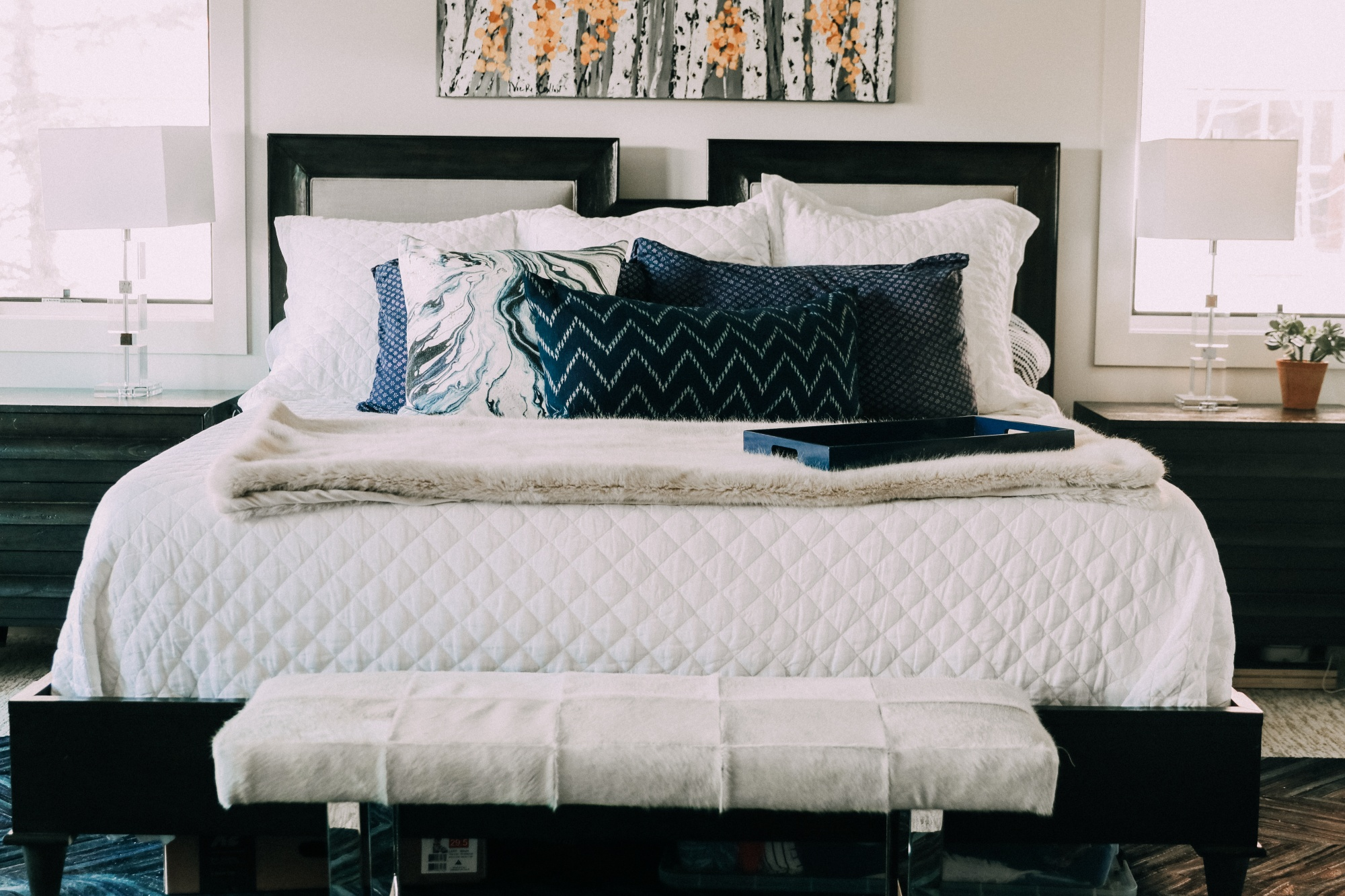 white and silver cowhide end of bed bench in master bedroom