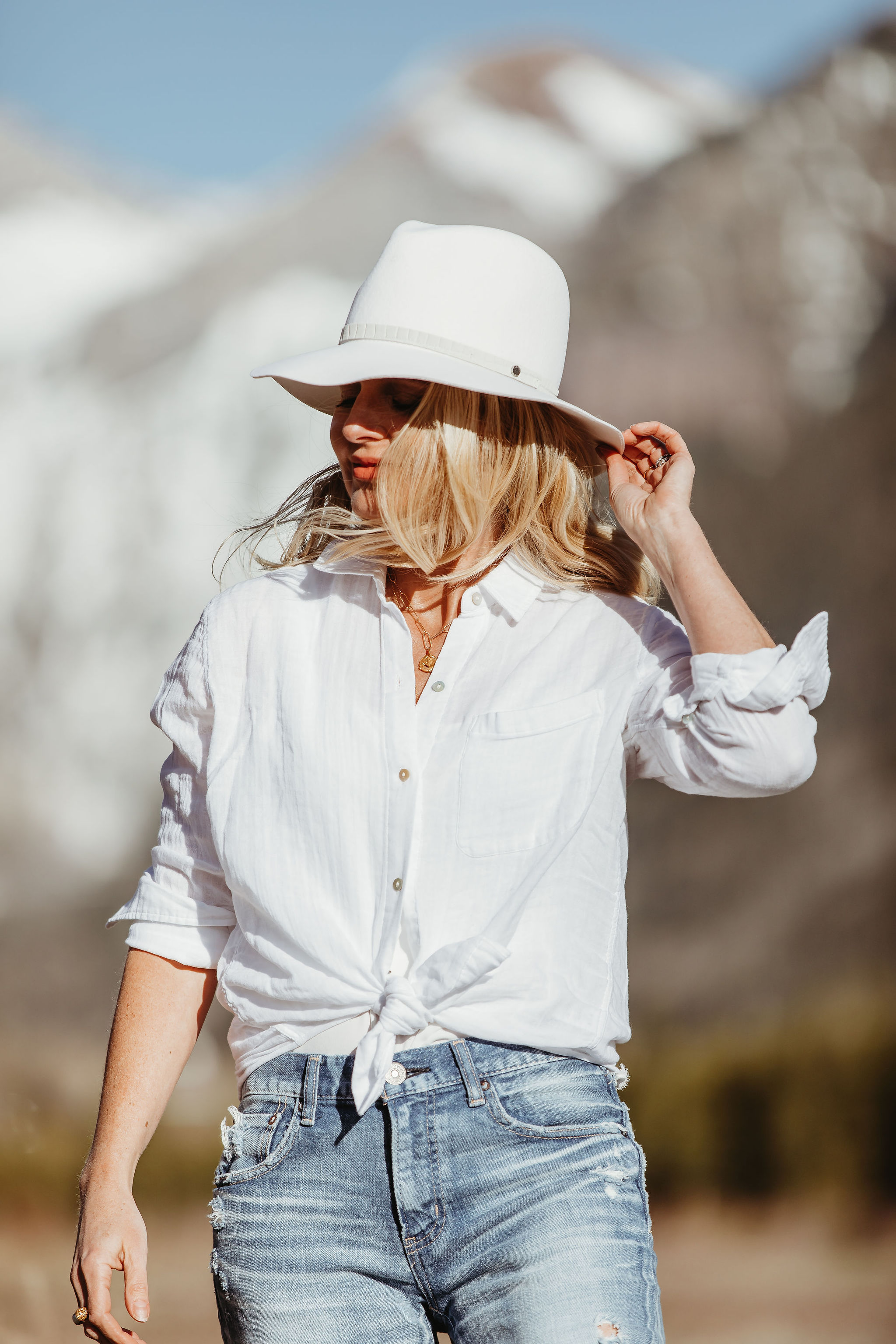 Africa Outfits, Erin Busbee of Busbee Style wearing a white cotton shirt by Rails with a white Rag & Bone hat and Moussy Vintage jeans in Telluride, CO