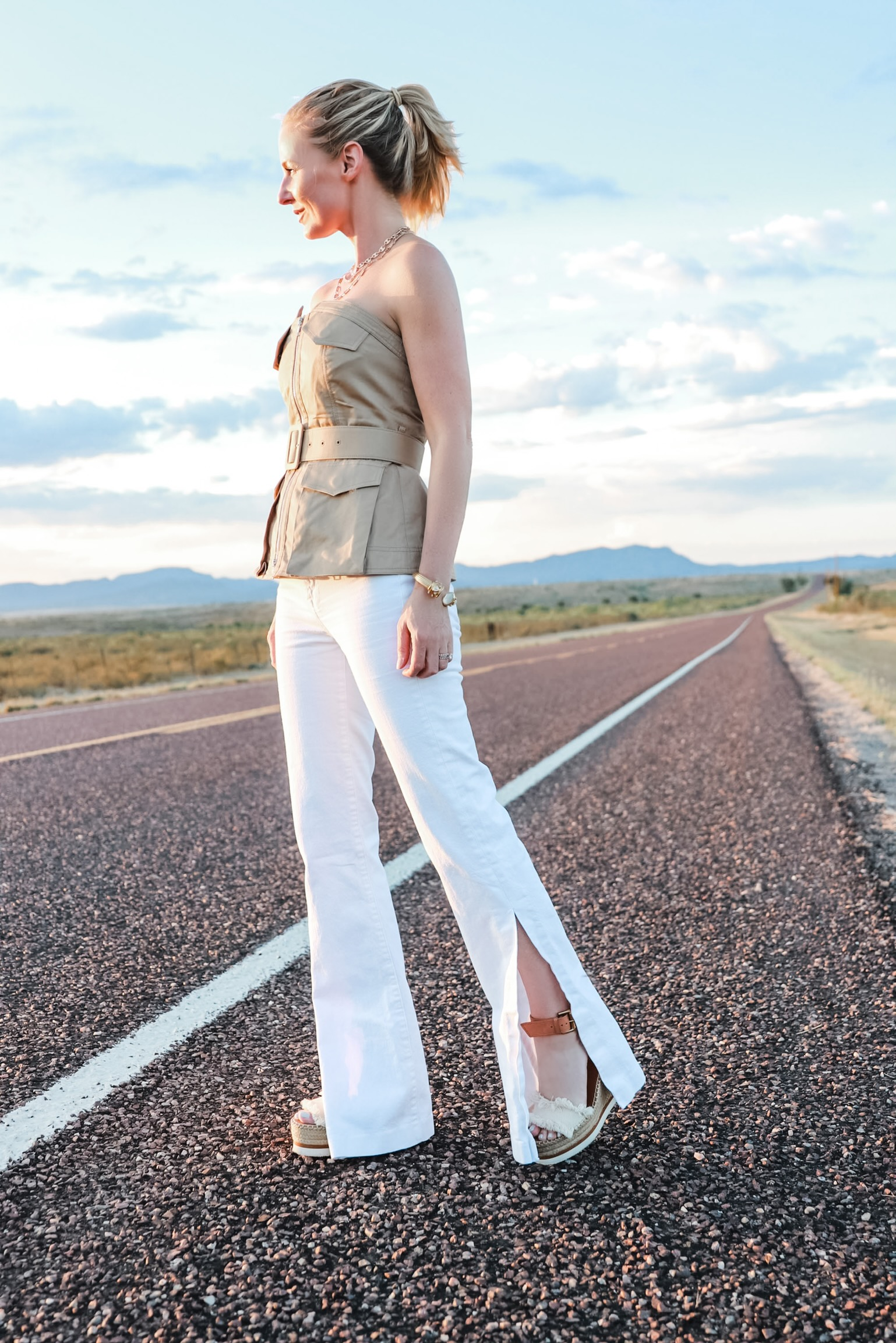 Africa Outfits, tan belted strapless Self Portrait shirt with white flare jeans and See By Chloe wedges