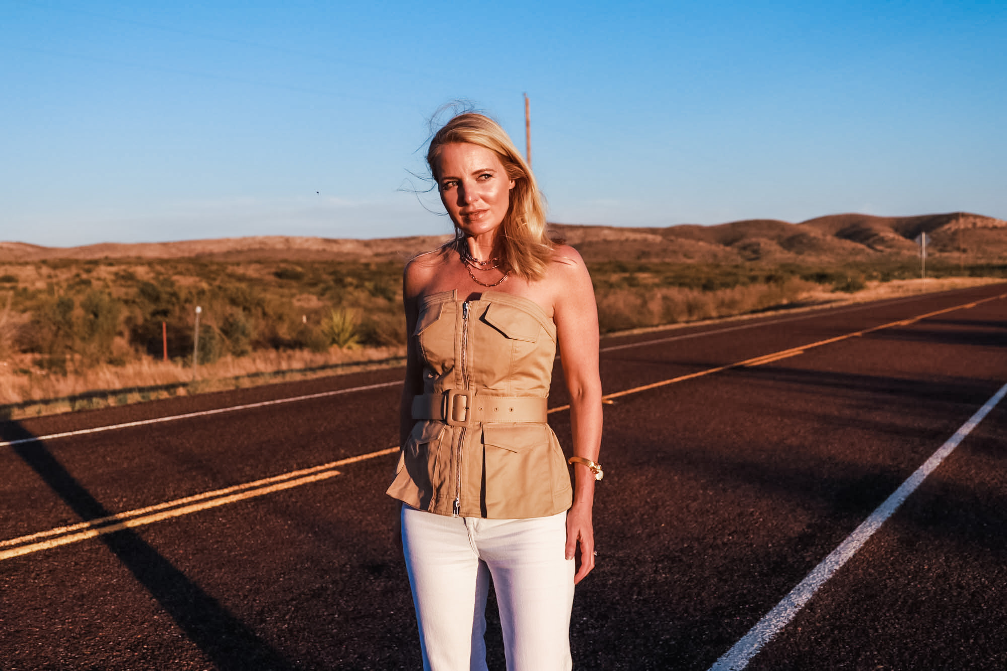 Africa Outfits, Erin Busbee of Busbee Style wearing a tan belted strapless utility trend shirt by Self Portrait with white flare jeans and See By Chloe wedges in Texas