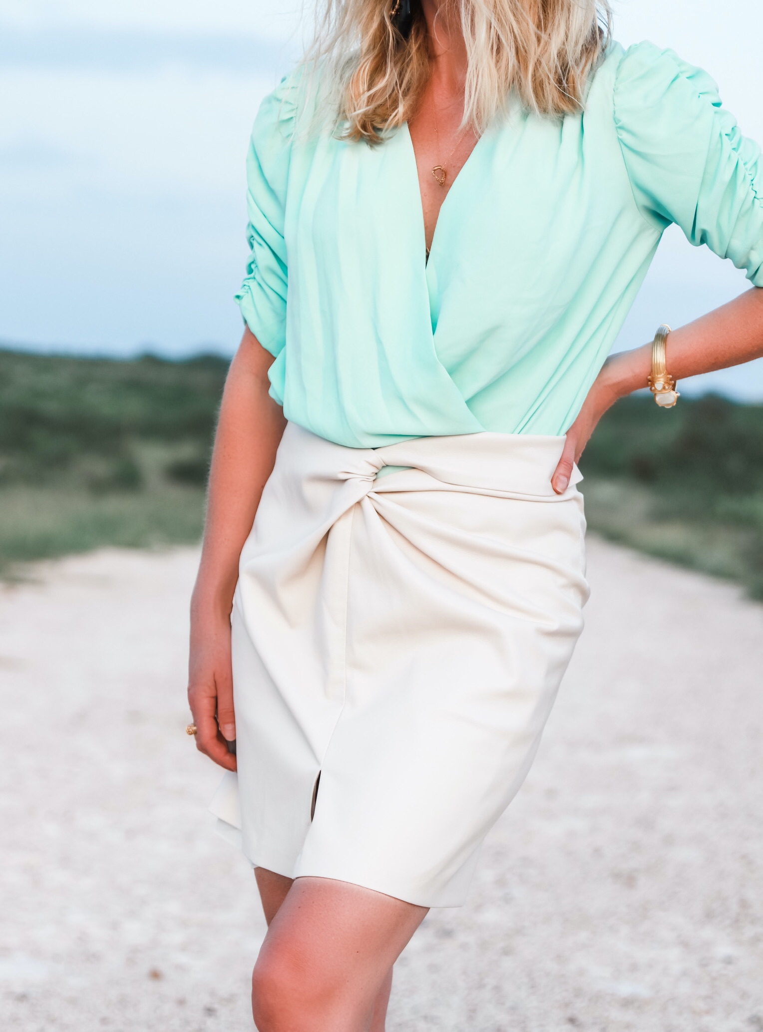 Nanushka Vegan leather Skirt, Fashion blogger Erin Busbee of Busbee Style wearing a mint green bodysuit by Amanda Uprichard, white vegan leather knotted skirt by nanushka, tortoise and pearl earrings by Elizabeth Cole, and white Botega Veneta sandals dupes standing on a ranch in south Texas