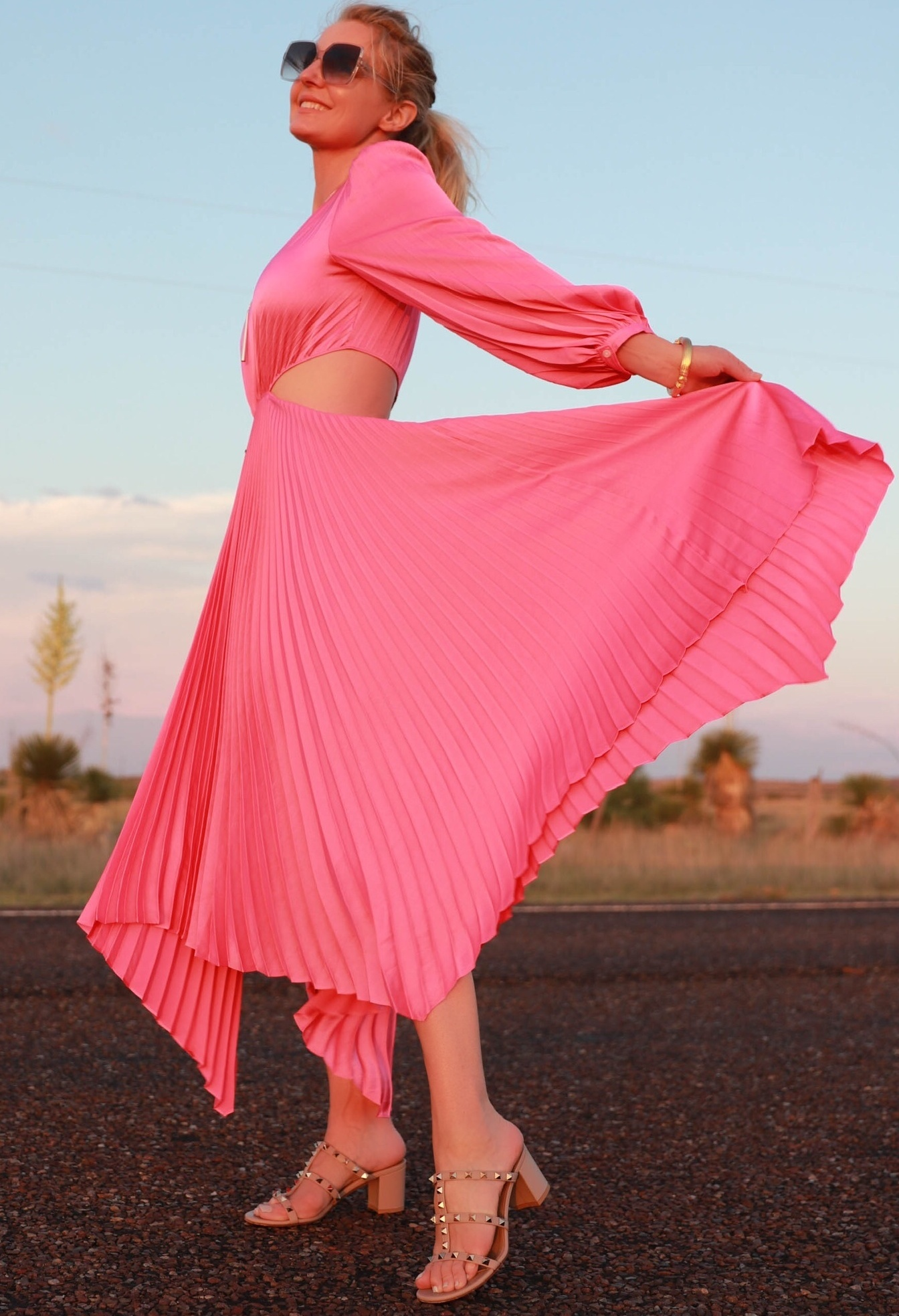 Pink Fashion Finds, Fashion blogger Erin Busbee of Busbee Style wearing a pink pleated dress by A.L.C. with Valentino Rockstud sandals walking in the road in South Texas