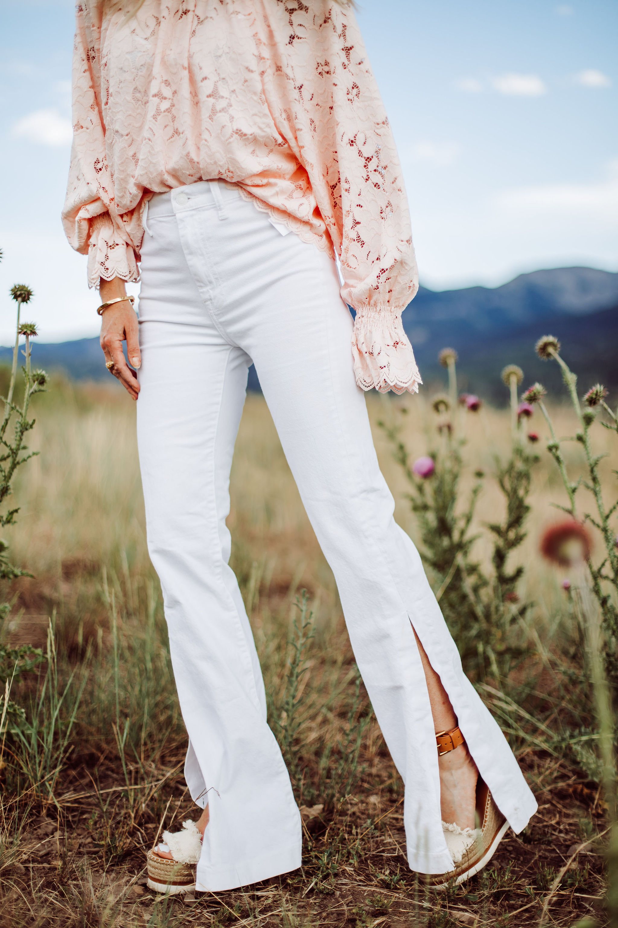 White Jeans for women Over 40, Fashion blogger Busbee Style wearing white 7 For All Mankind split hem jeans, See by Chloe espadrille wedges, pink lace long sleeve Free People top in Telluride, Colorado