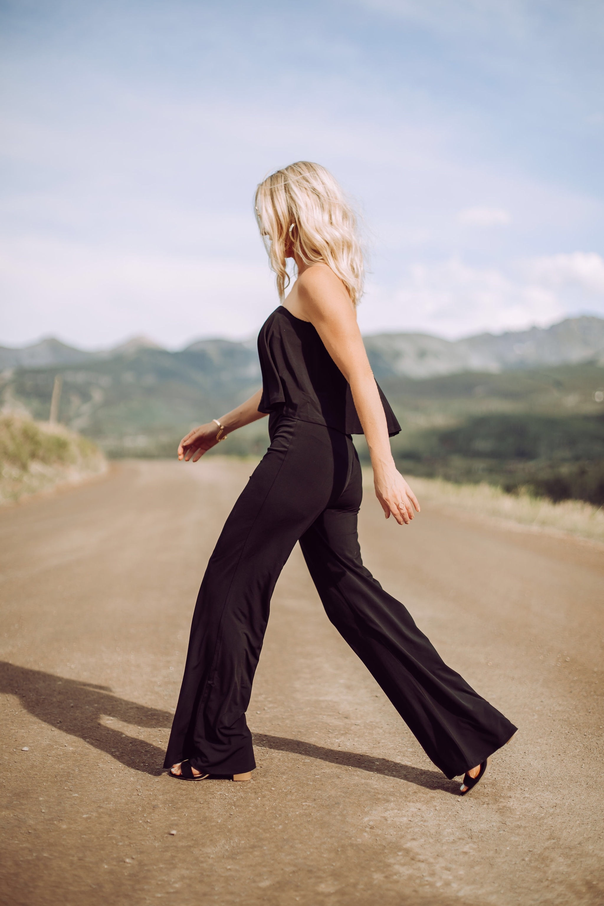 Jumpsuits Over 40, Fashion Blogger Erin Busbee of Busbee Style wearing a black flared jumpsuit by Scoop and black strappy block heel sandals by Scoop from Walmart walking in Telluride, Colorado