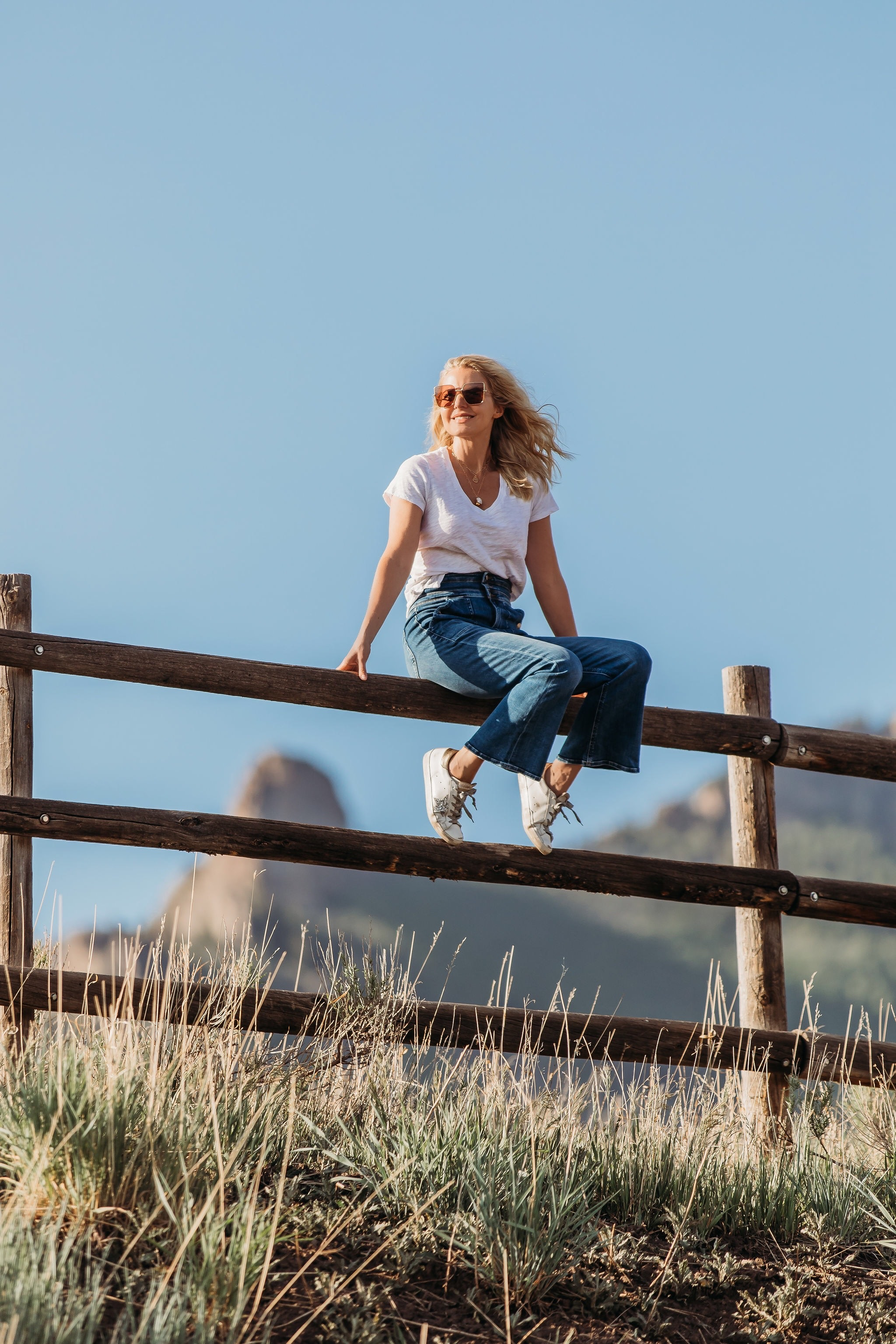 Summer Mom Style, Fashion blogger Erin Busbee of Busbee Style wearing a white v-neck tee with wide leg flare jeans by Frame, Golden Goose sneakers, Julie Vos bracelets, Aligheri necklaces, and Saint Laurent sunglasses in Telluride, Colorado