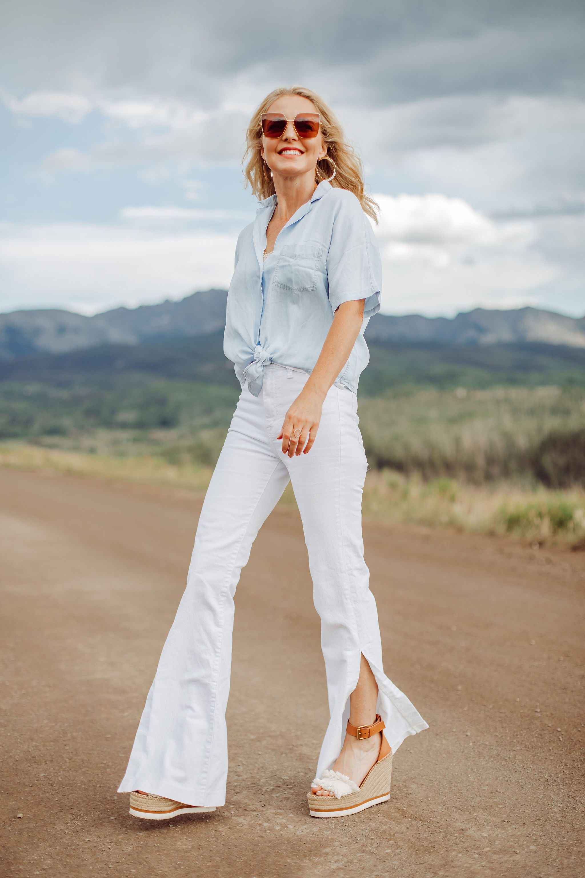 Blouses That Cover Arms, Fashion blogger Erin Busbee of Busbee Style wearing a blue tie-front button down shirt by Rails with high waisted white slit hem jeans by 7 For All Mankind and See by Chloe wedges and Saint Laurent sunglasses in Telluride, Colorado