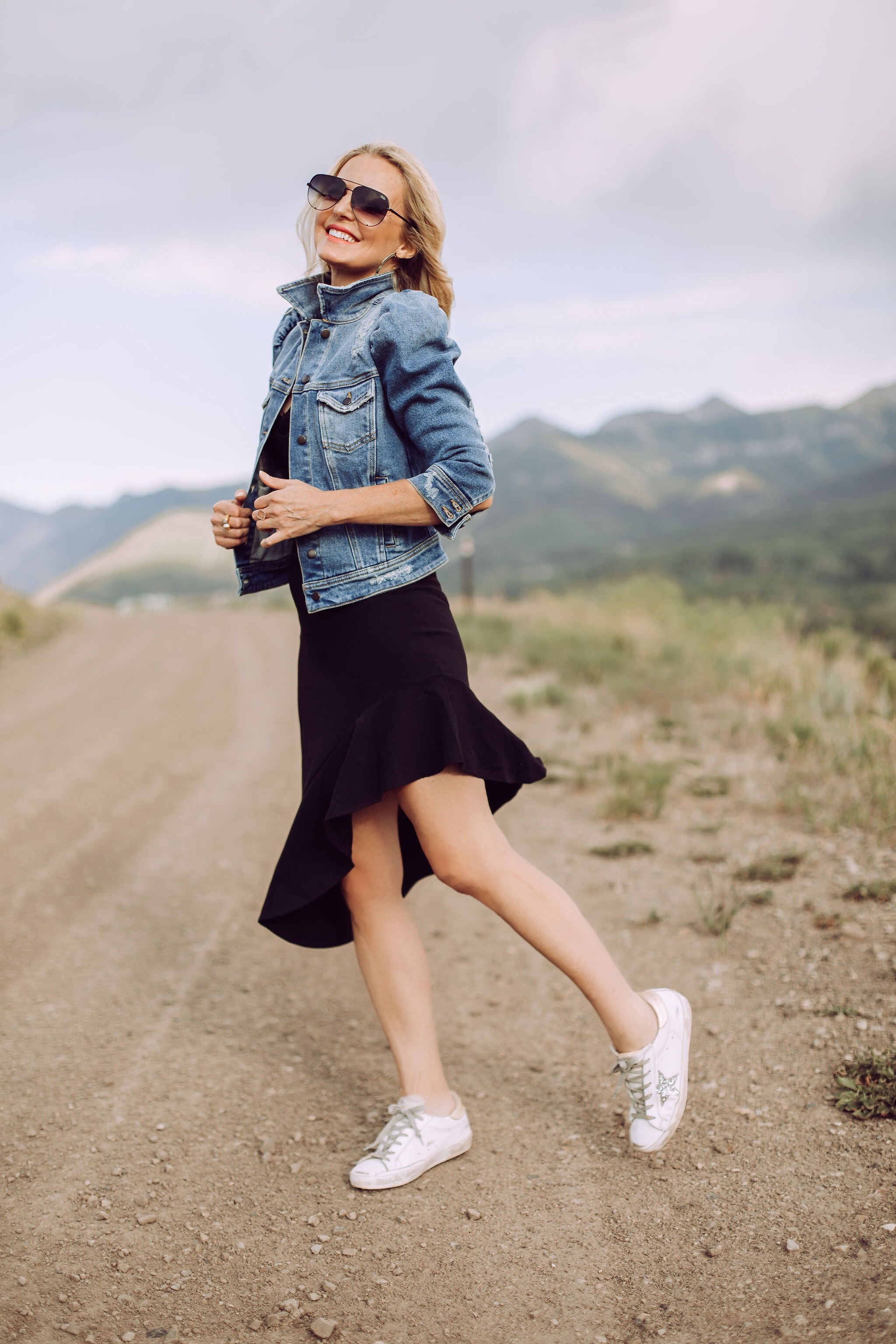 Day To Date Night Outfits, Fashion blogger Erin Busbee of Busbee Style wearing a black susana monaco dress with golden goose sneakers, retrofete denim puff sleeve jacket and aviator sunglasses in Telluride, Colorado