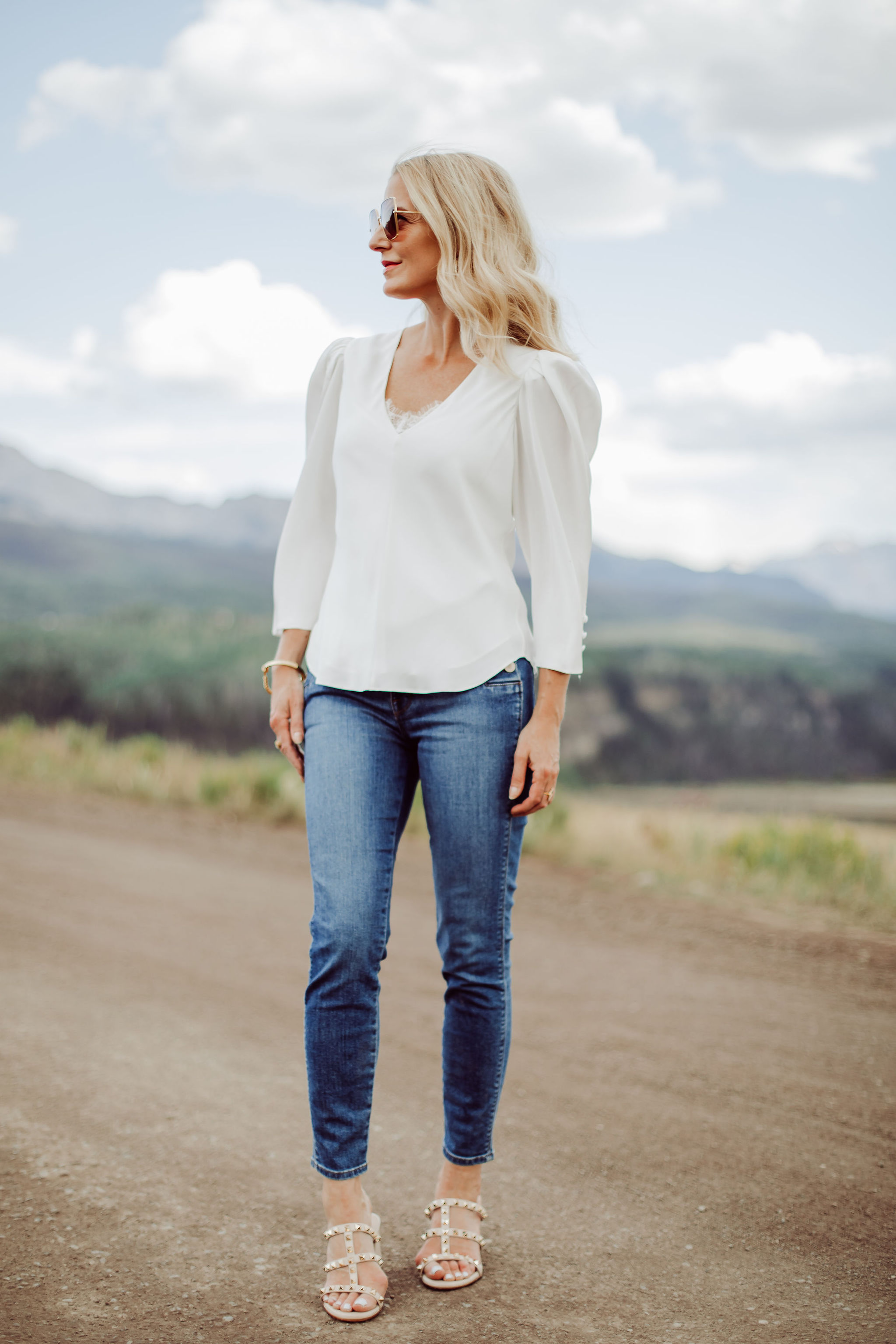 Frame Blouses, Fashion blogger Erin Busbee of Busbee Style wearing a white puff sleeve blouse by Frame with Valentino sandals and J Brand Natasha jeans in Telluride, Colorado