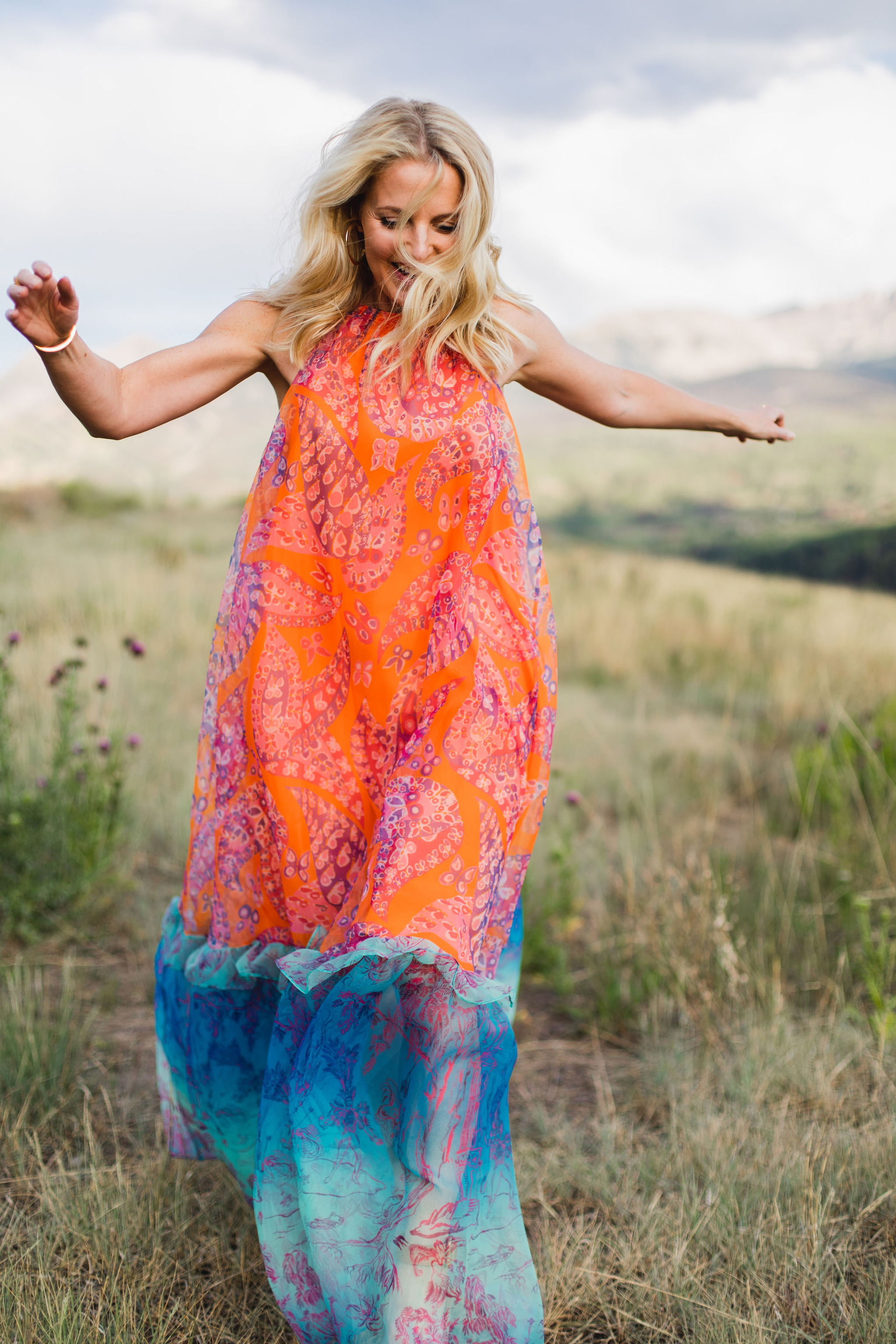How To Manifest Anything, Fashion blogger Erin Busbee of Busbee Style wearing an orange and blue Staud Ina dress with white sunglasses walking around in Telluride, Colorado