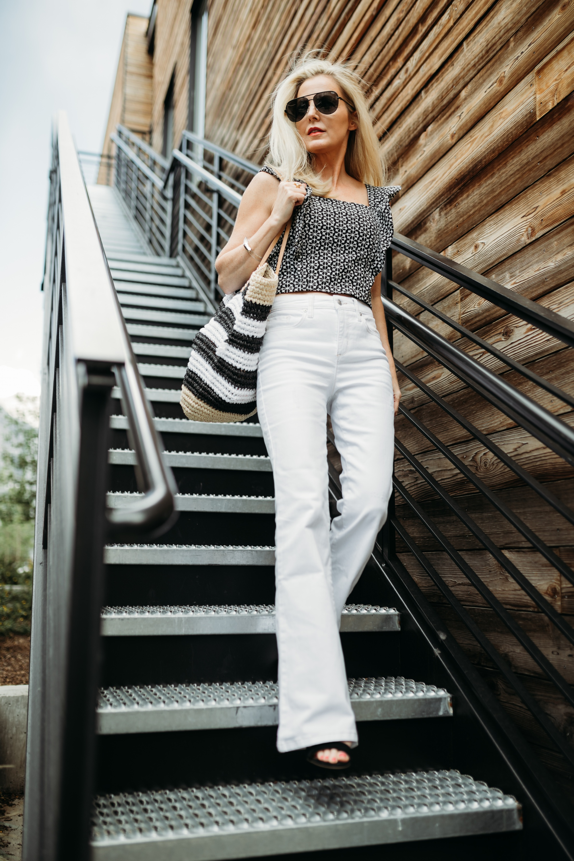 How to Make Legs Look Longer, Fashion blogger Erin Busbee of Busbee Style wearing white flared jeans, printed ruffle sleeve top, black strappy block heel sandals, and striped tote bag by Scoop from Walmart in Telluride, Colorado