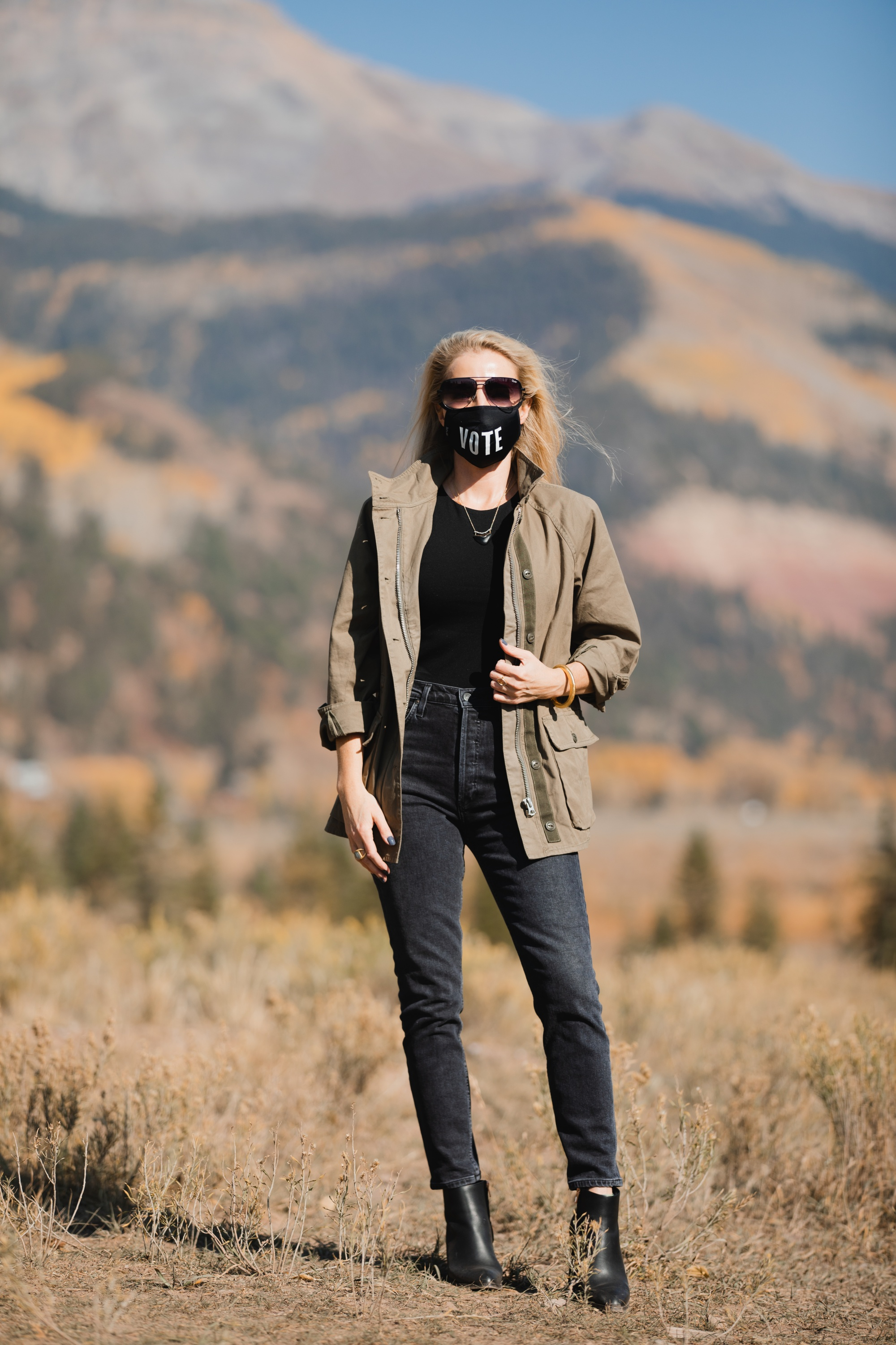How To Wear A Cargo Jacket, Erin Busbee of Busbee Style wearing a green cargo jacket by rag & bone, black muscle tee tank by Aqua, gray wash Nico slim fit jeans by Agolde, QUAY sunglasses, Vote mask, and Alexander Wang cutout booties from Bloomingdale's in Telluride, Colorado