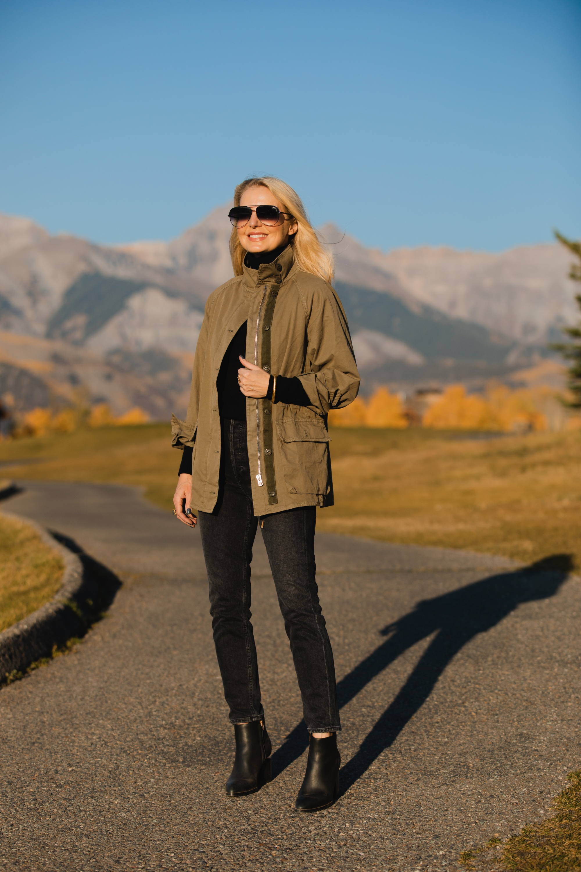 How To Wear A Cargo Jacket, Erin Busbee of Busbee Style wearing a green cargo jacket by rag & bone, black turtleneck puff sleeve cashmere sweater by Aqua, gray wash Nico slim fit jeans by Agolde, QUAY sunglasses, and Alexander Wang cutout booties in Telluride, Colorado