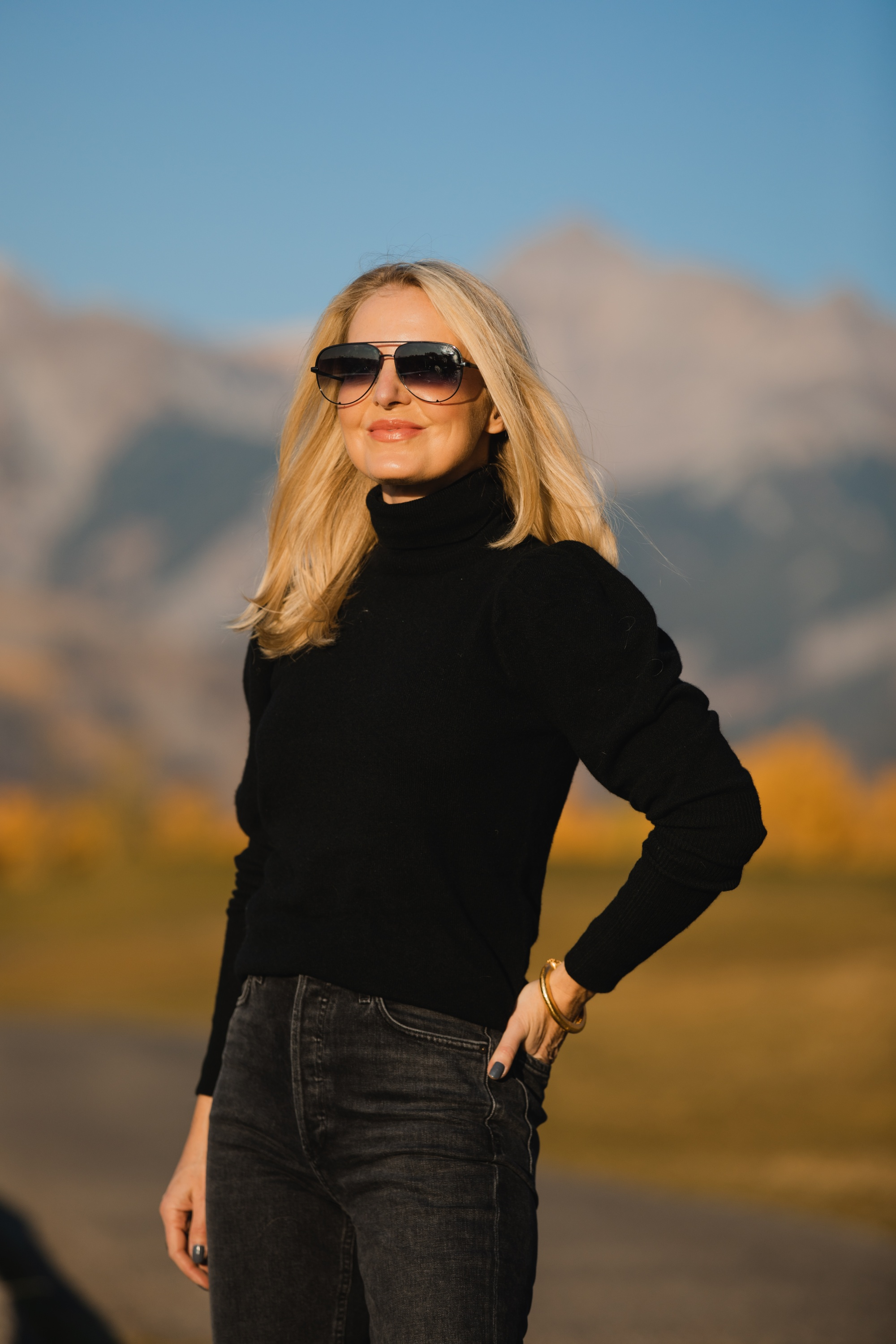 How To Wear A Cargo Jacket, Erin Busbee of Busbee Style wearing a black turtleneck puff sleeve cashmere sweater by Aqua, gray wash Nico slim fit jeans by Agolde, QUAY sunglasses, and Alexander Wang cutout booties in Telluride, Colorado