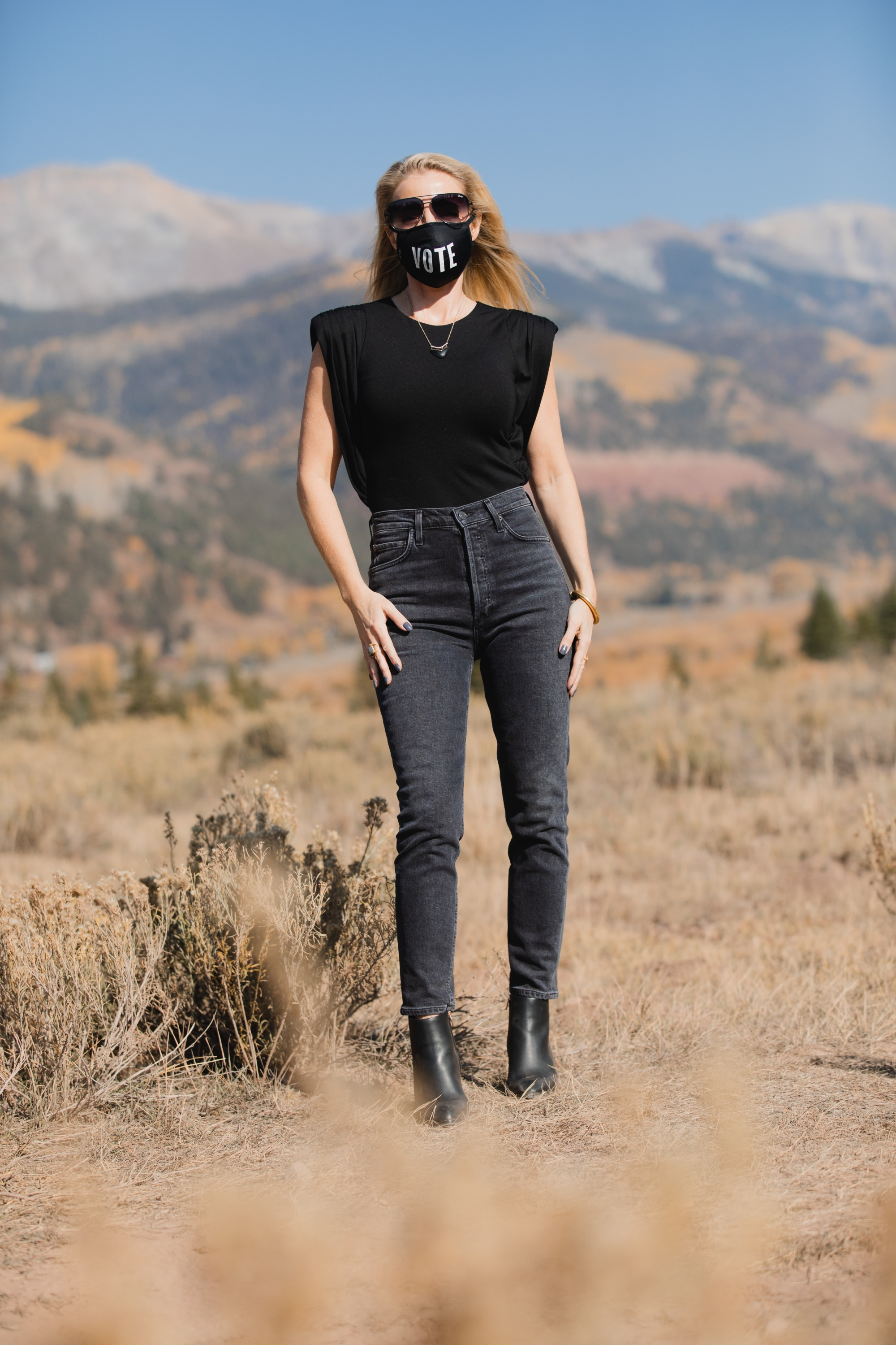 How To Wear A Cargo Jacket, Erin Busbee of Busbee Style wearing a black muscle tee tank by Aqua, gray wash Nico slim fit jeans by Agolde, QUAY sunglasses, Vote mask, and Alexander Wang cutout booties from Bloomingdale's in Telluride, Colorado