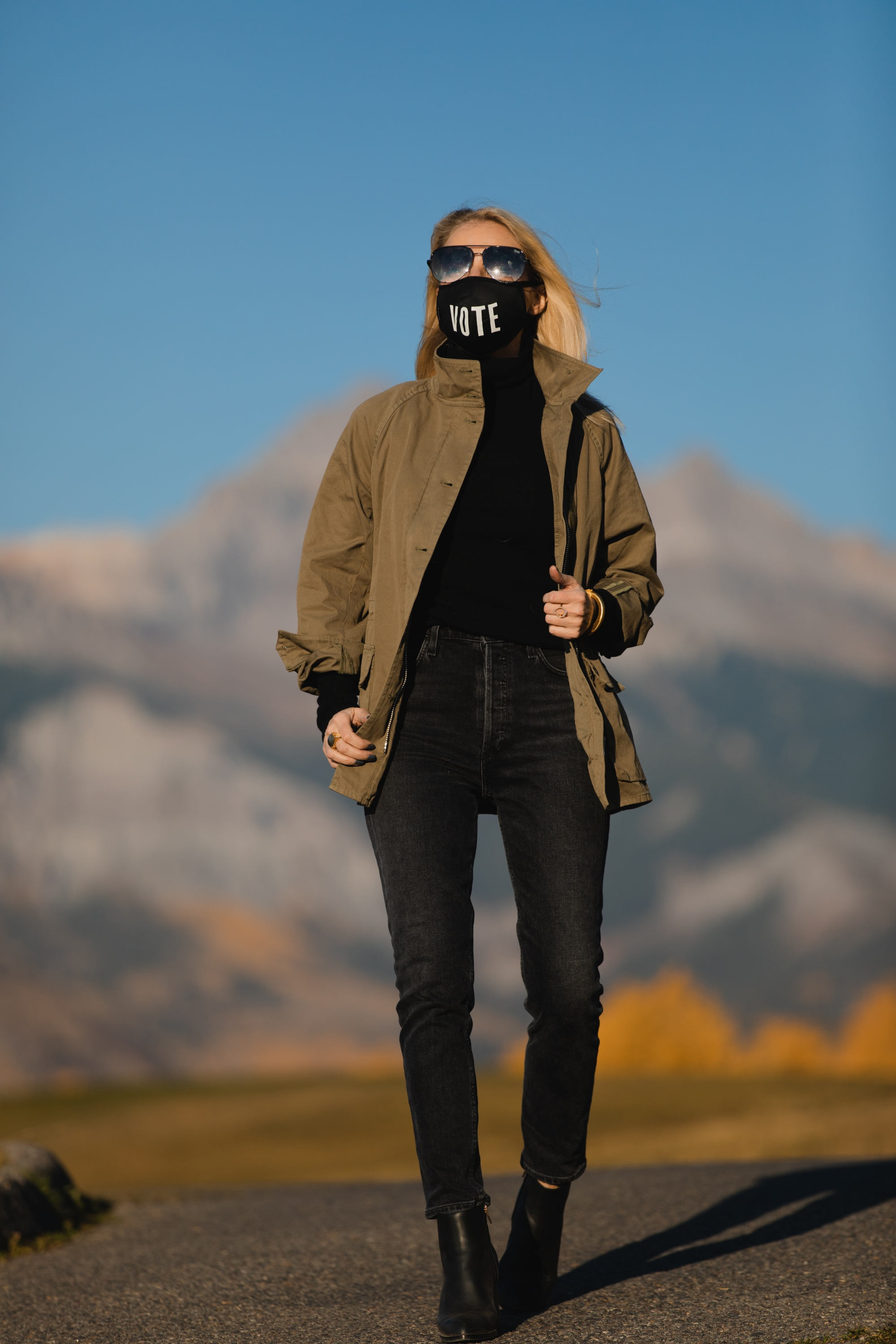 How To Wear A Cargo Jacket, Erin Busbee of Busbee Style wearing a green cargo jacket by rag & bone, black turtleneck puff sleeve cashmere sweater by Aqua, gray wash Nico slim fit jeans by Agolde, QUAY sunglasses, Vote mask, and Alexander Wang cutout booties from Bloomingdale's in Telluride, Colorado