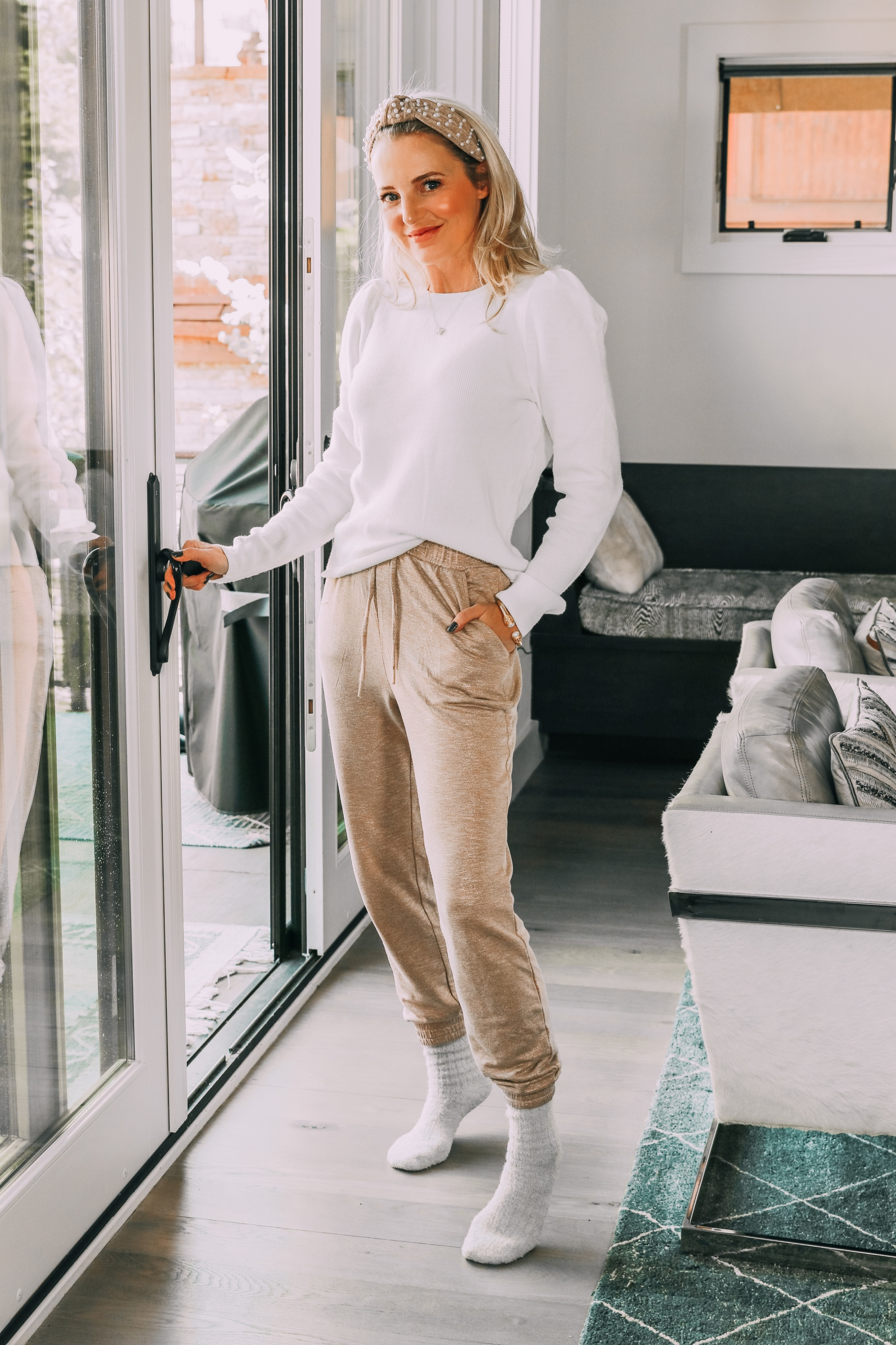 Stylish Loungewear, Erin Busbee of Busbee Style wearing tan metallic jogger pants, a white puff sleeve sweater, beige fuzzy socks, and a pearl beaded headband from Express in her living room in Telluride, Colorado