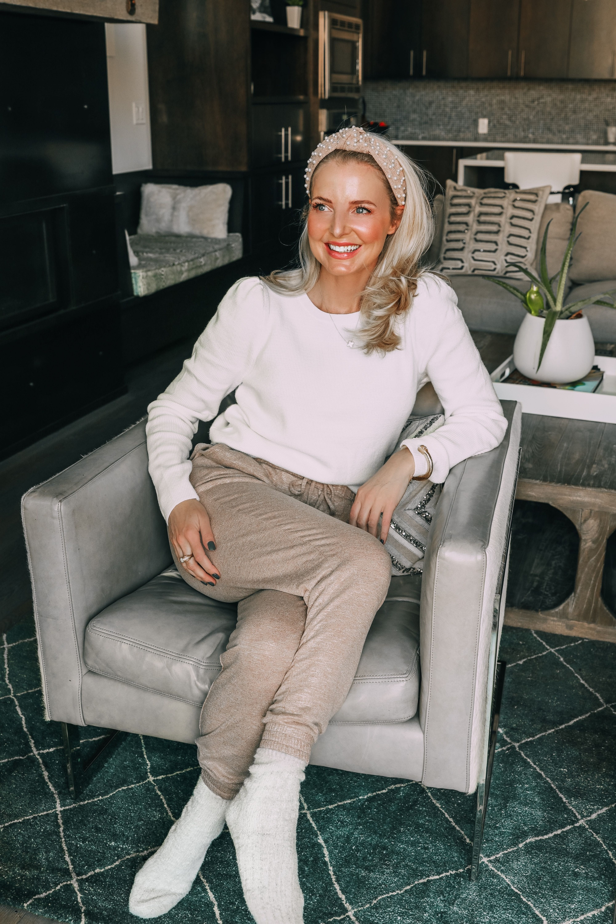 Loungewear over 40, how to look chic and polished fashion over 40 blogger Erin Busbee wearing Express metallic joggers and white ribbed puff shoulder sweater with pearl headband and fuzzy socks