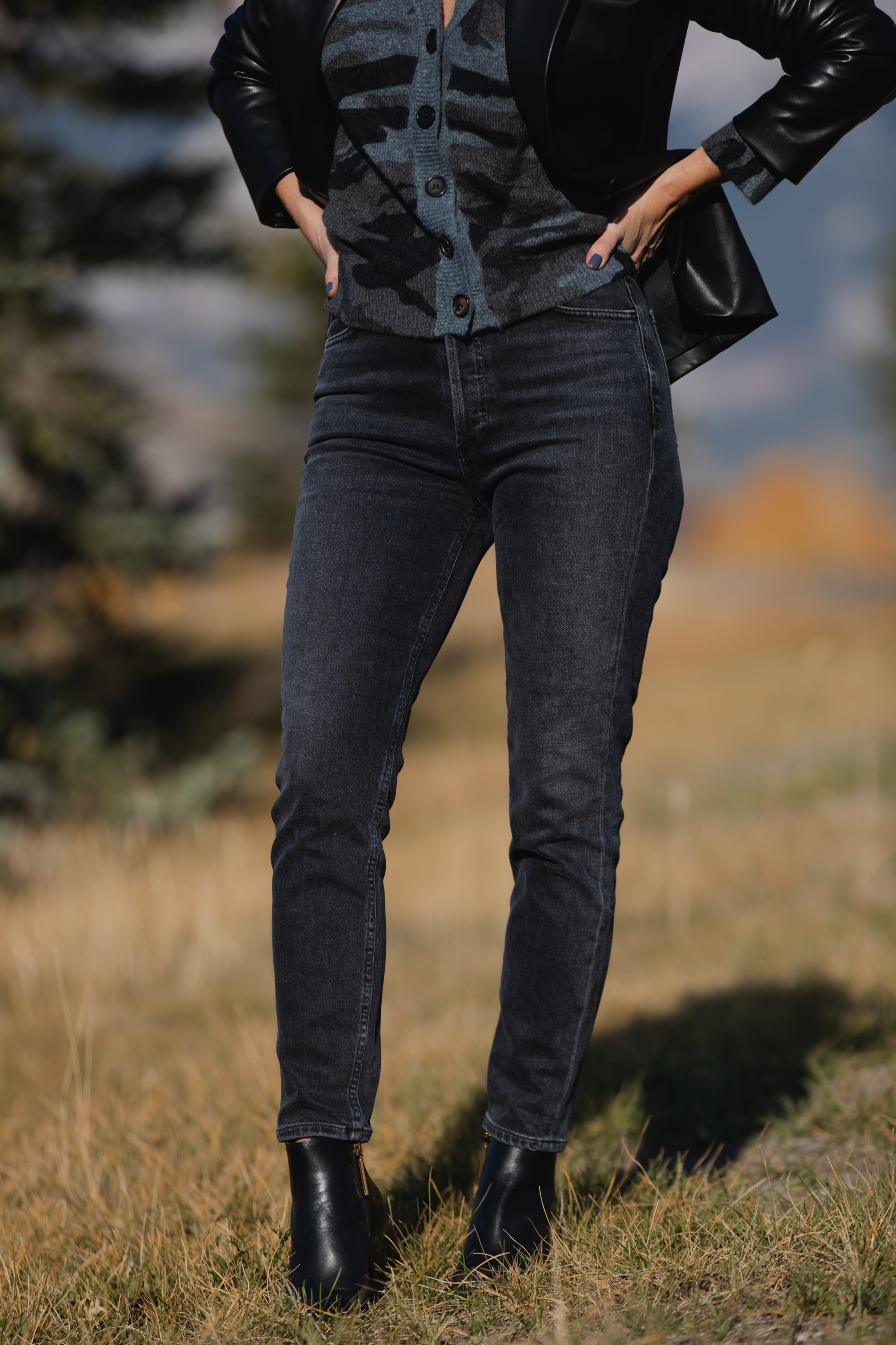 Favorite Fall Jackets, Erin Busbee of Busbee Style holding a black faux leather blazer by Theory and wearing dark gray wash Agolde Nico jeans, black Louise et Cie booties, and Rails camo cardigan sweater in Telluride, Colorado