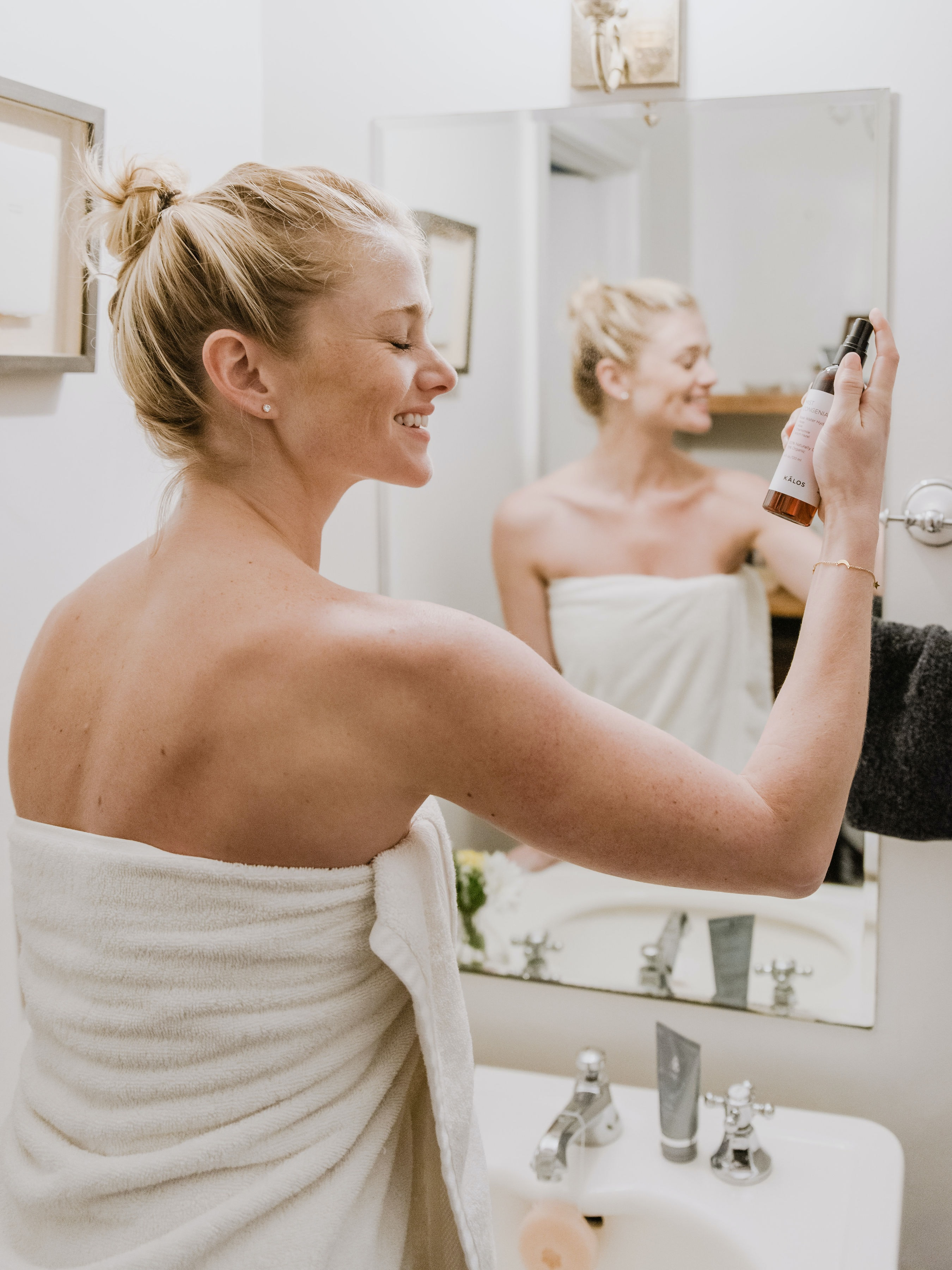Spend time on yourself first, Blonde woman with hair in bun in bathroom spraying face with beauty product taking time for self care, start saying no