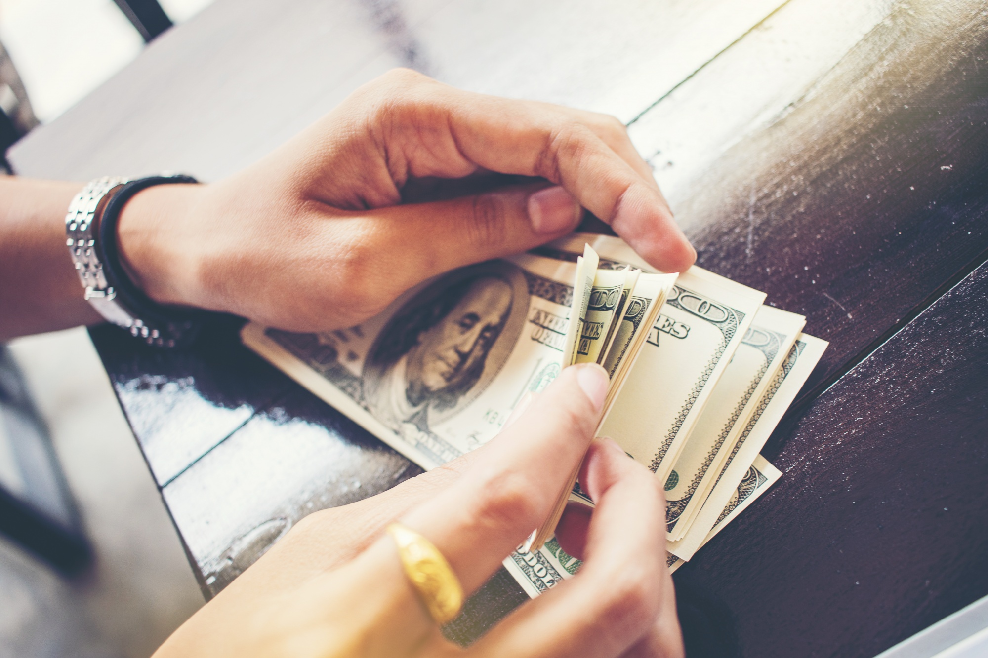 creating financial security, woman counting cash holding in her hands
