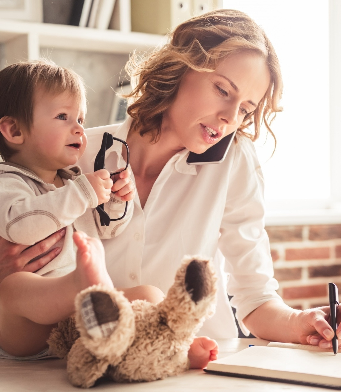 What Saying NO Can Do, blonde woman working and writing holding her baby who has taken glasses and has a stuffed animal