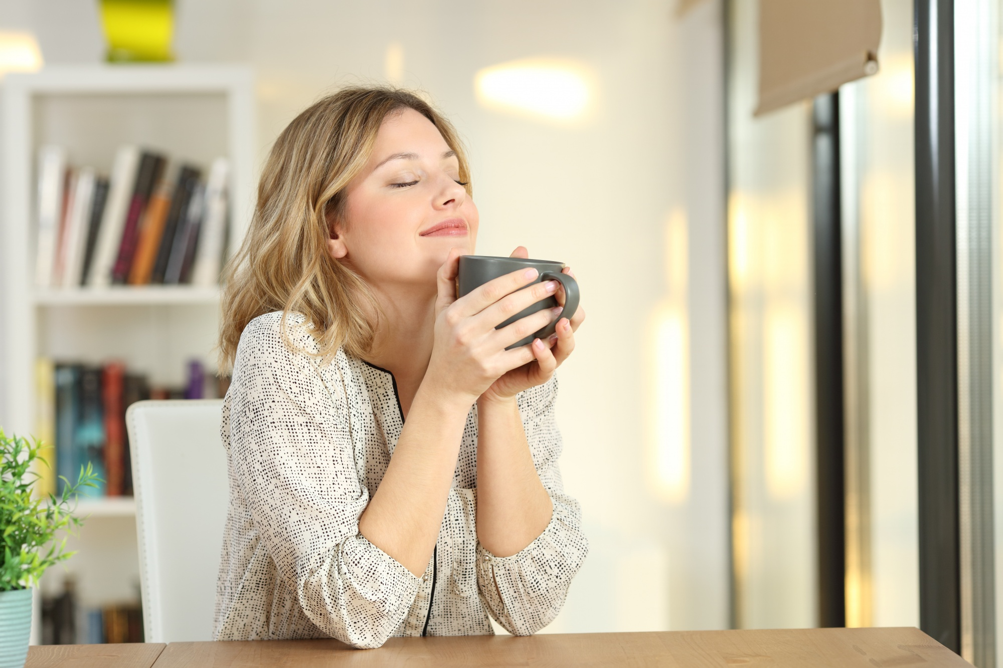 Blonde woman cradling a hot beverage with her eyes closed enjoying the moment