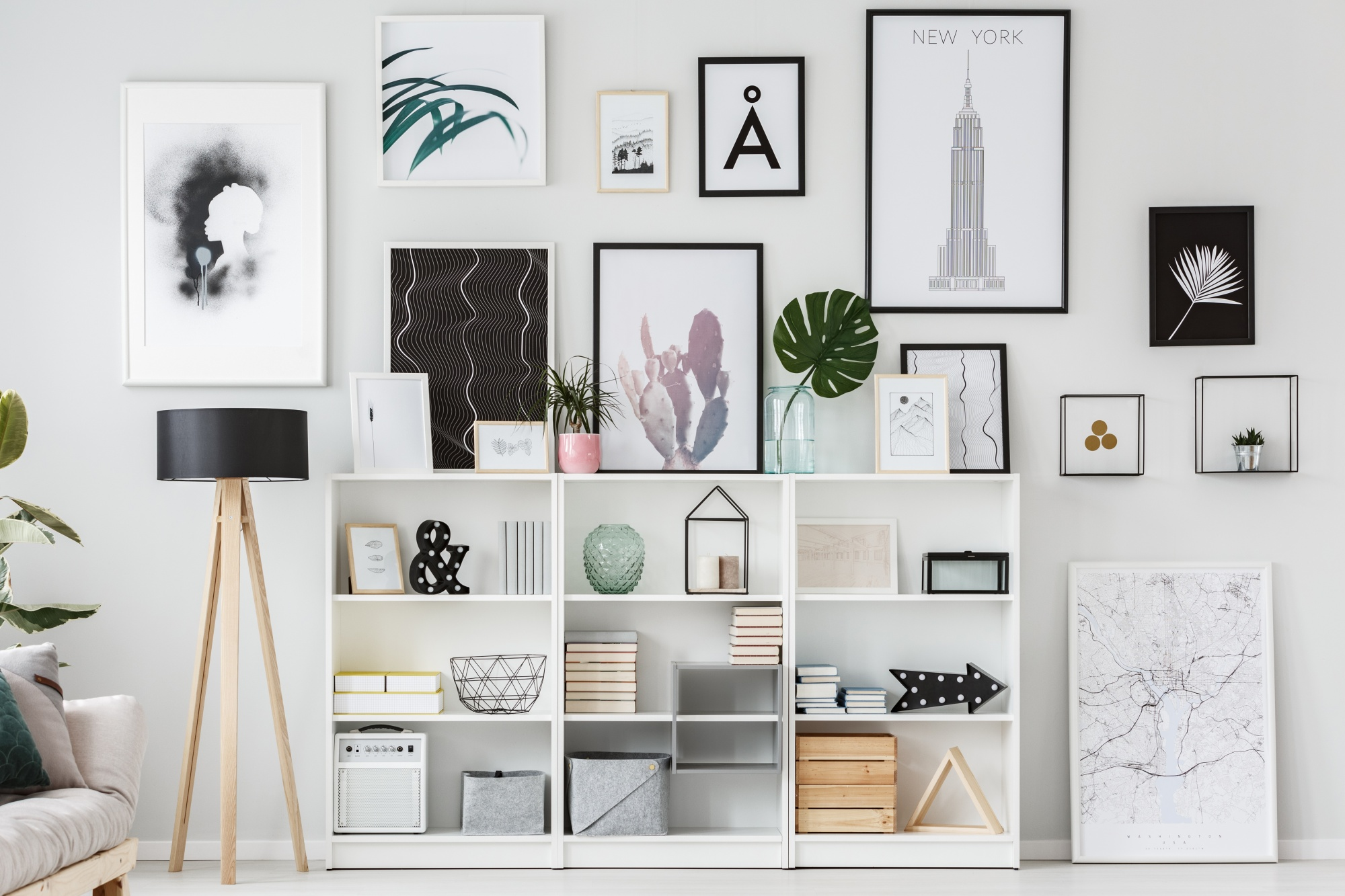 5 Easy Steps To The Perfect and Unique Gallery Wall with a black and white and floral theme showing pieces leaning up against shelves and propped on the floor for a full ceiling to floor look which includes white shelving