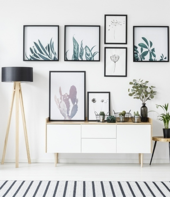5 Easy Steps To The Perfect and Unique Gallery Wall with botanical posters and perfect spacing between framed artwork against an all white wall and a console below providing a great layout example