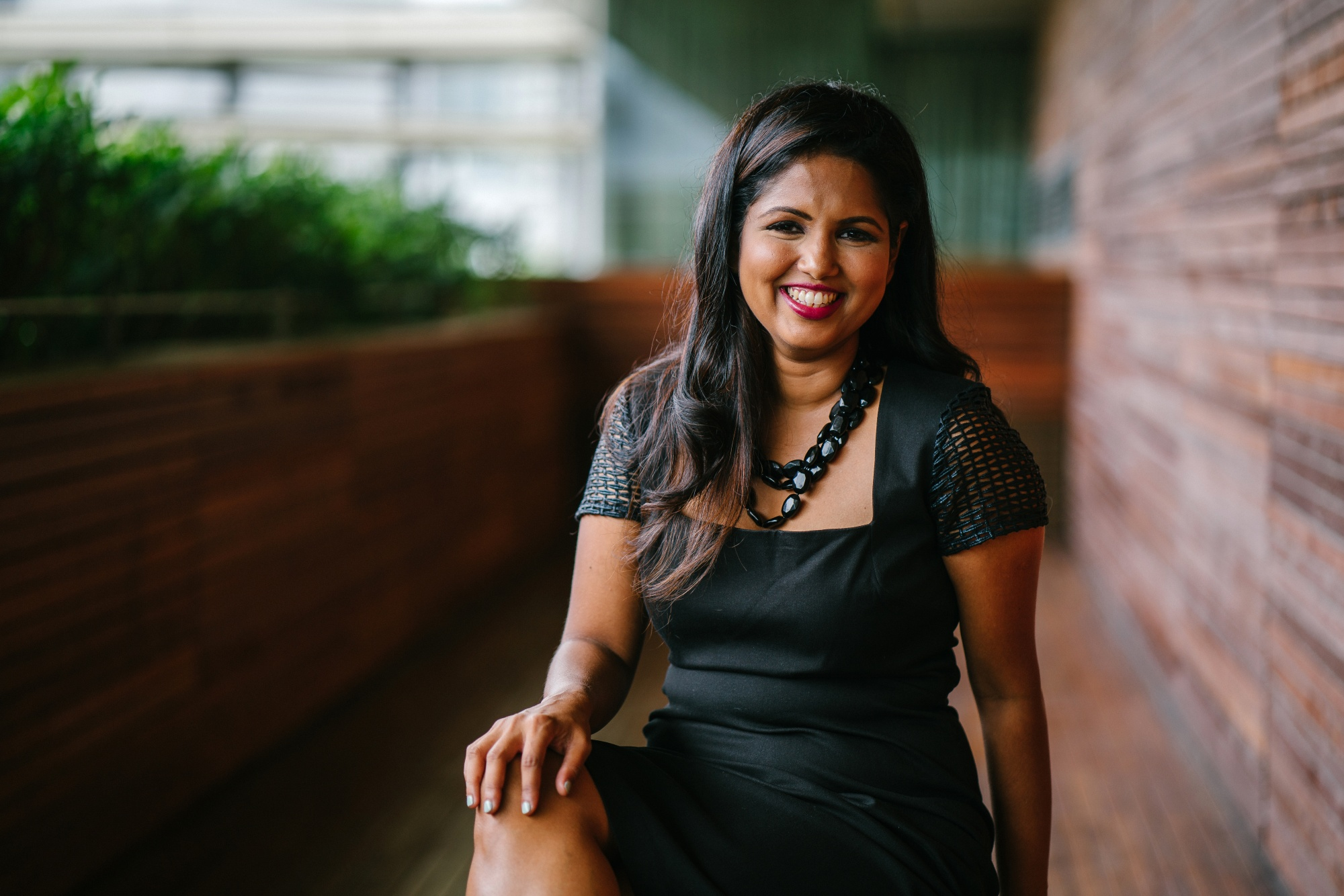 New Year's Resolutions, Long-haired Indian woman in black dress near a brick wall