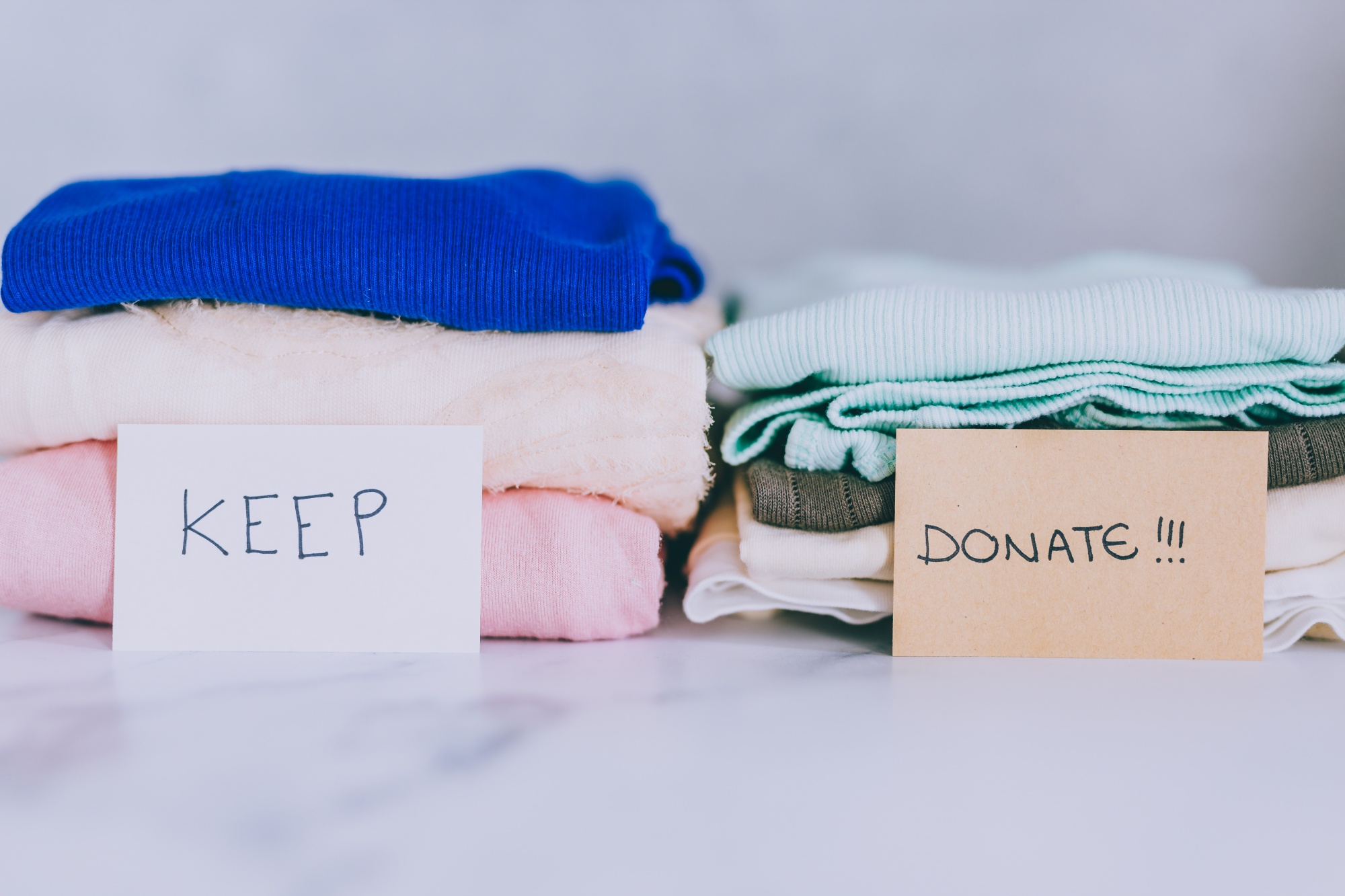 The Best Way To Get Organized Before Holiday Chaos Ensues by organzing stacks of clothing to donate vs those to keep