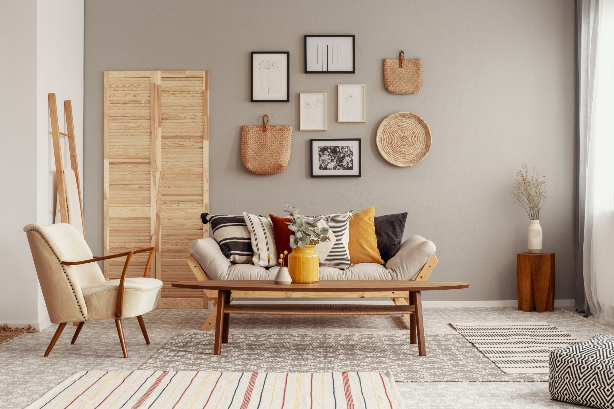 5 Easy Steps To The Perfect and Unique Gallery Wall including hanging baskets and photographs in neutral colors against a light grey wall with wooden shutters and a wooden ladder off to the side