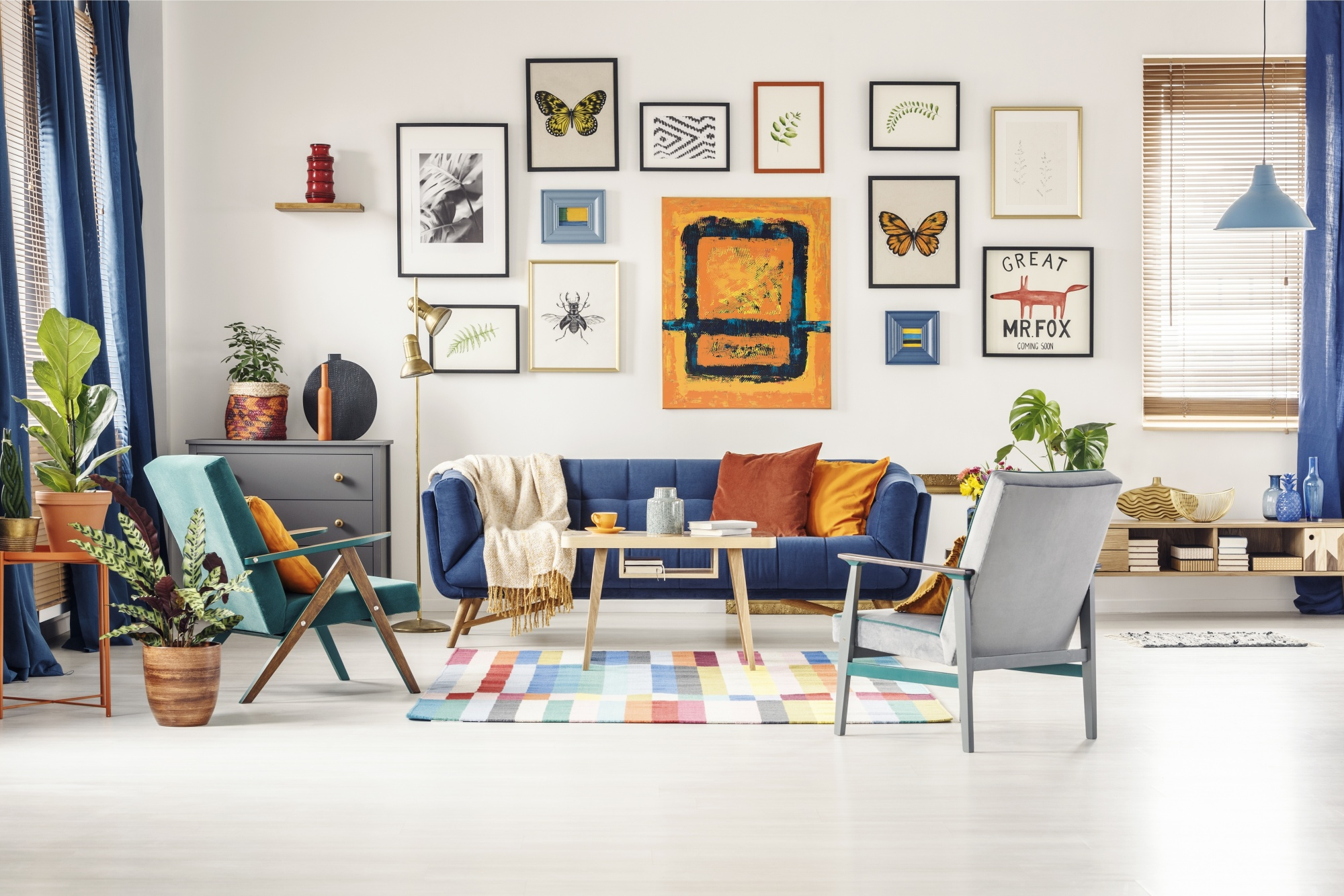 5 Easy Steps To The Perfect and Unique Gallery Wall above a blue couch with multiple artistic images and butterflies framed against an all white wall
