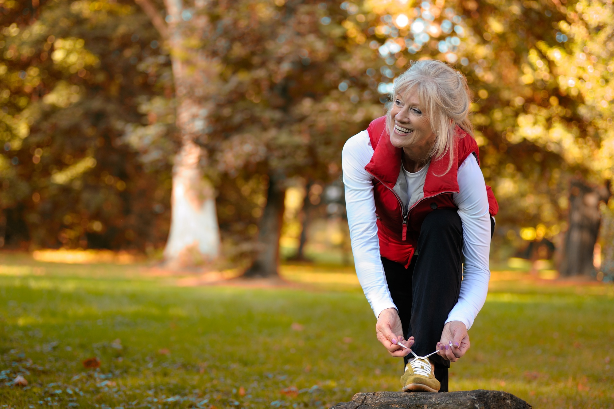 New Year's Resolutions, Blond woman getting ready for a run in black pants, white shirt, and red vest