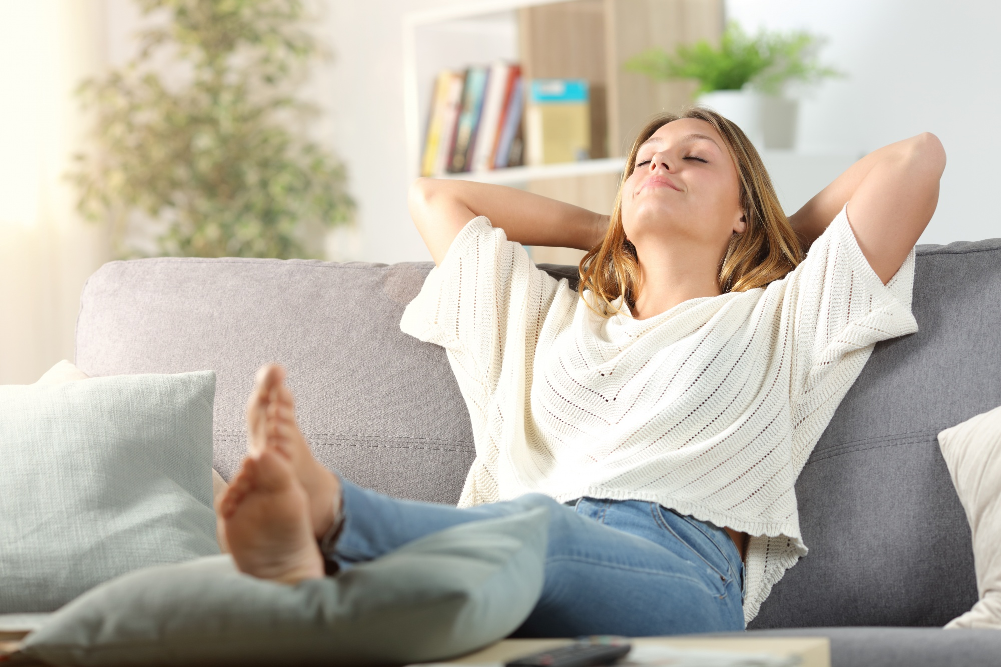 New Year's Resolutions, Carefree woman relaxing sitting on a sofa at home in jeans and blousy white top