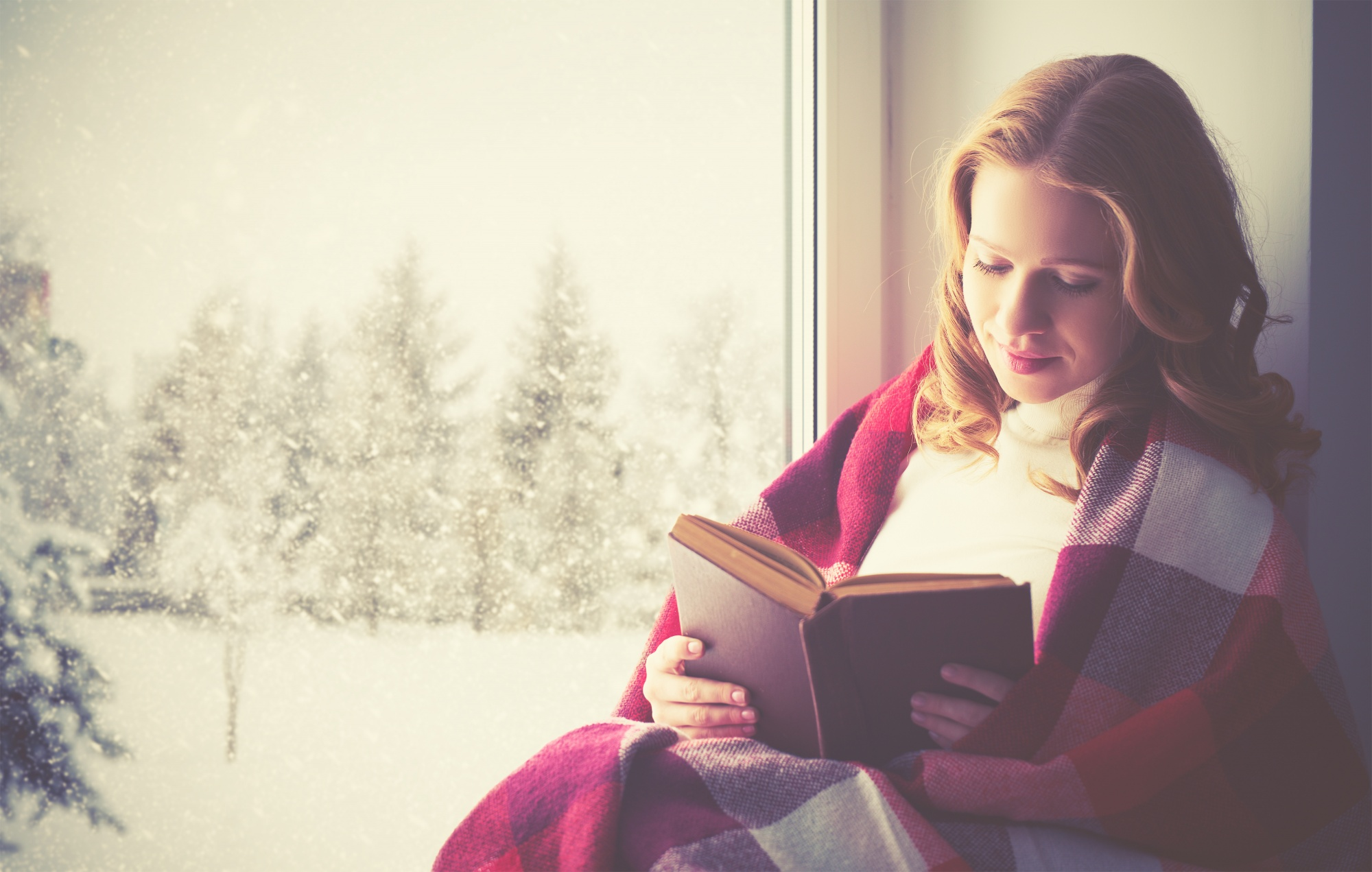 Happy woman reading a book by the window in the winter wrapped in red blanket