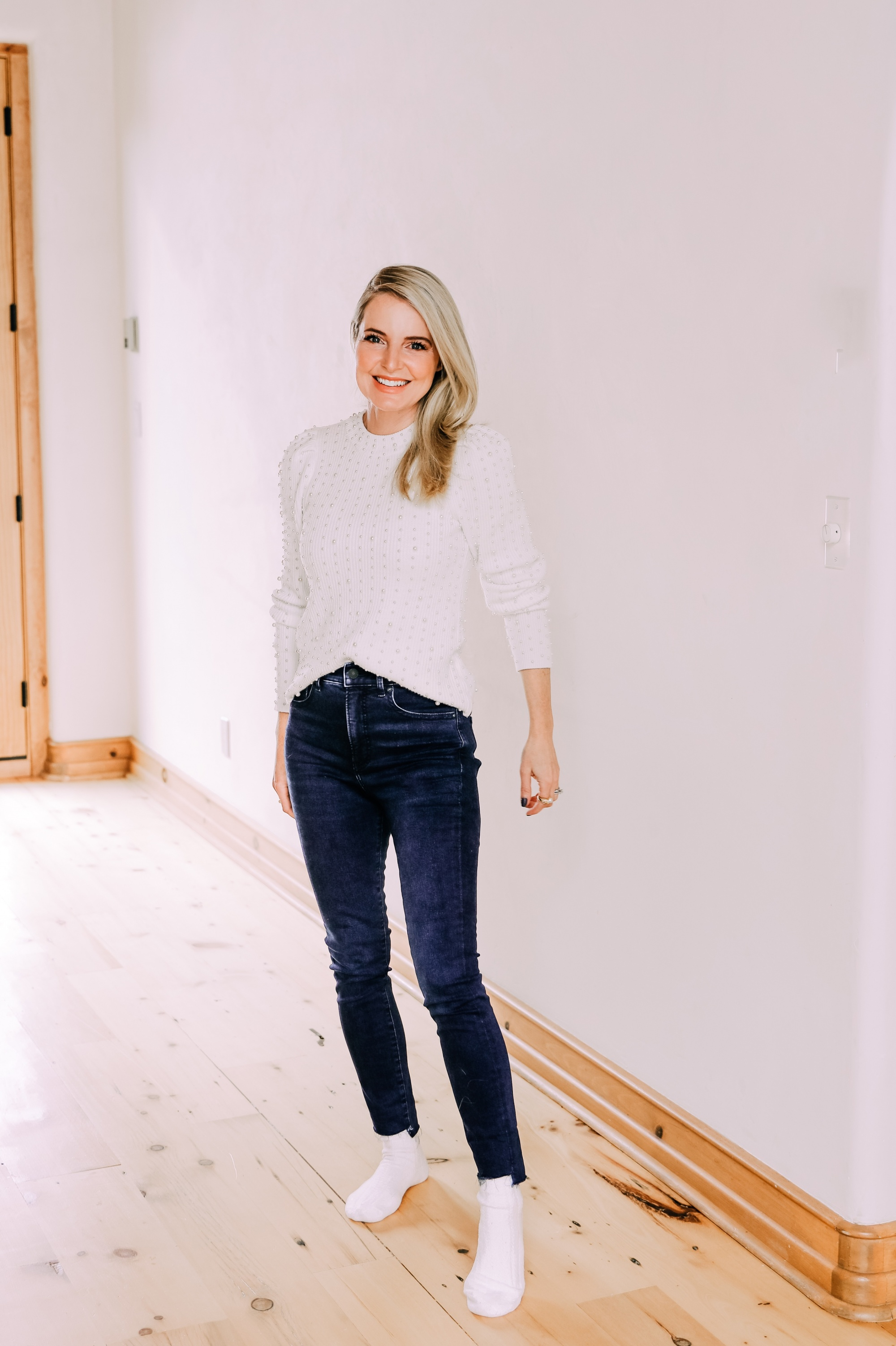 Black Friday Doorbuster, Erin Busbee of Busbee Style wearing a pearl embellished white sweater, raw step hem jeans, and cozy socks from Express in Telluride, Colorado