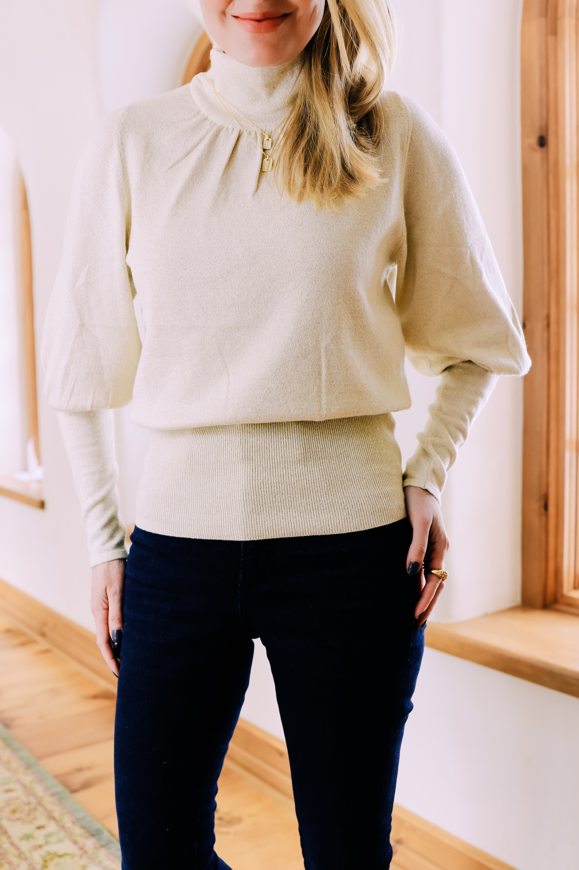 Black Friday Doorbuster, Erin Busbee of Busbee Style wearing a metallic blouson sleeve turtleneck sweater, raw step hem jeans, pave layered dog tag necklace, and cozy socks from Express in Telluride, Colorado