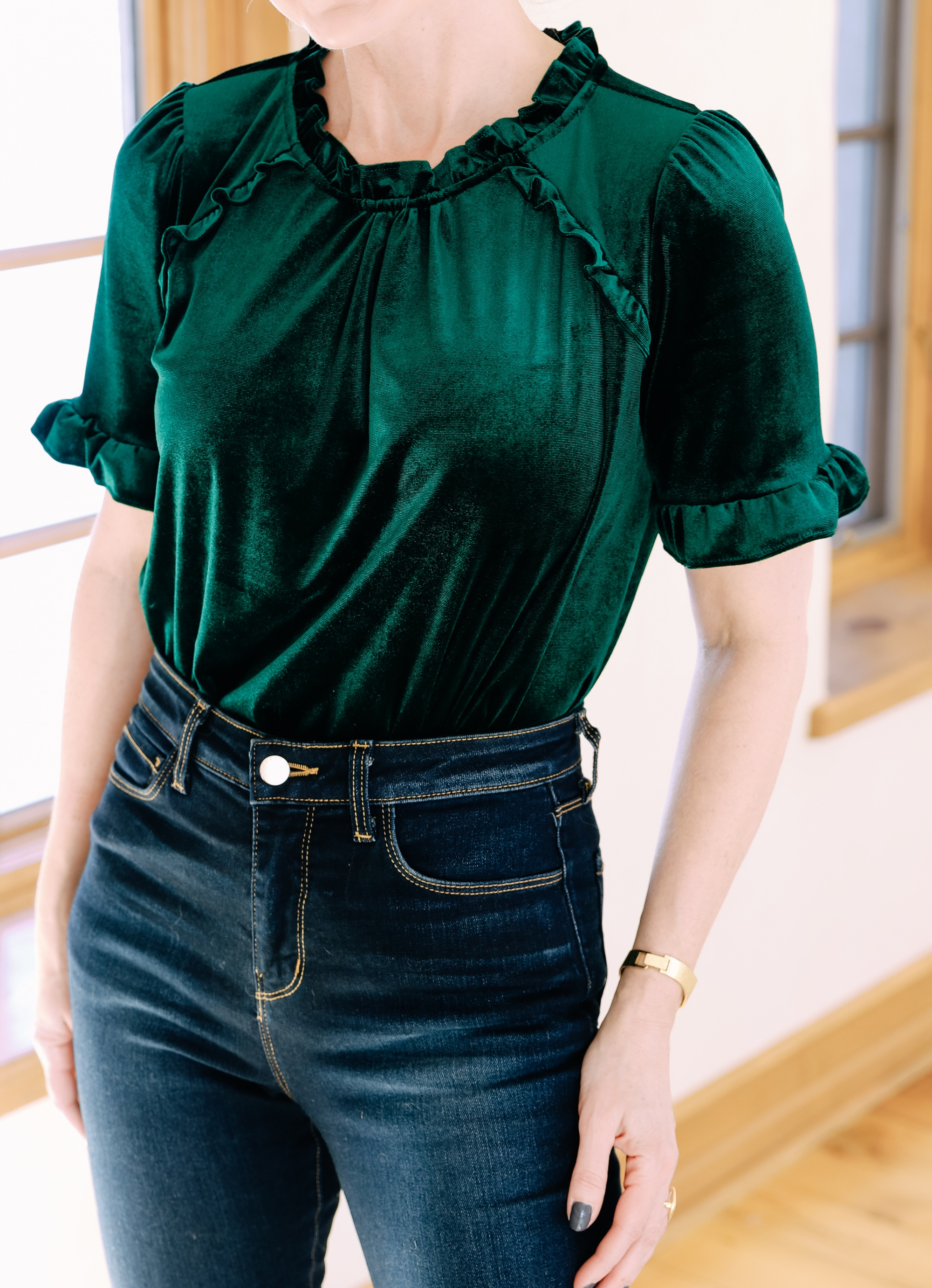 Holiday Outfits With Jeans, Erin Busbee of Busbee Style wearing a green velvet ruffle sleeve blouse by Gibson, L'Agence dark wash skinny jeans, and black Jimmy Choo Romy pumps from Nordstrom in Telluride, Colorado