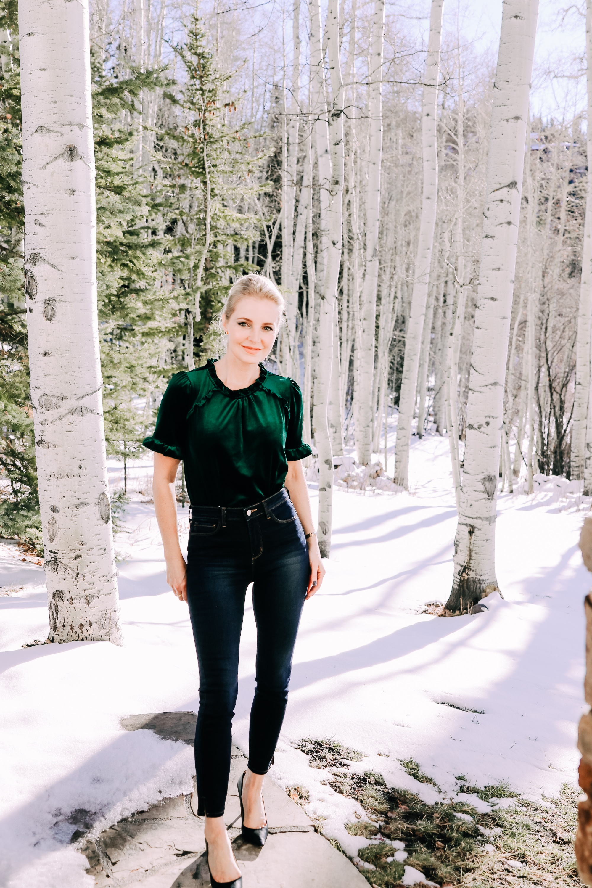 Holiday Outfits With Jeans, Erin Busbee of Busbee Style wearing a green velvet ruffle sleeve blouse by Gibson, L'Agence dark wash skinny jeans, and black Jimmy Choo Romy pumps from Nordstrom outside in the snow in Telluride, Colorado