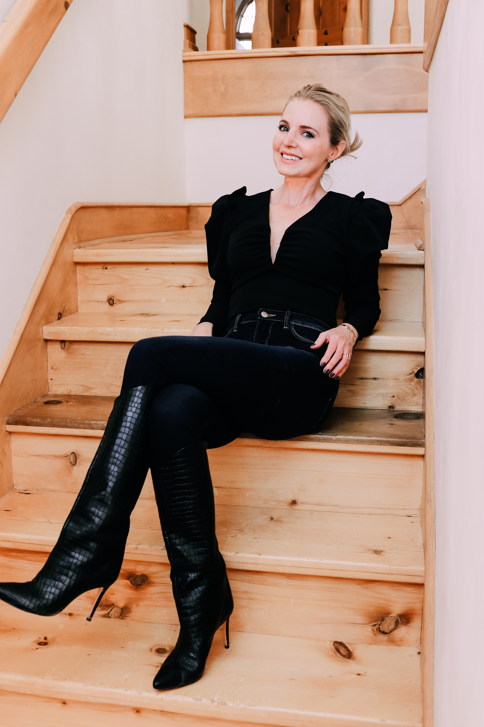 Holiday Outfits With Jeans, Erin Busbee of Busbee Style wearing a black ASTR the Label puff sleeve bodysuit, L'Agence dark wash skinny jeans, and black snake embossed boots by Schutz from Nordstrom sitting on the stairs in Telluride, Colorado