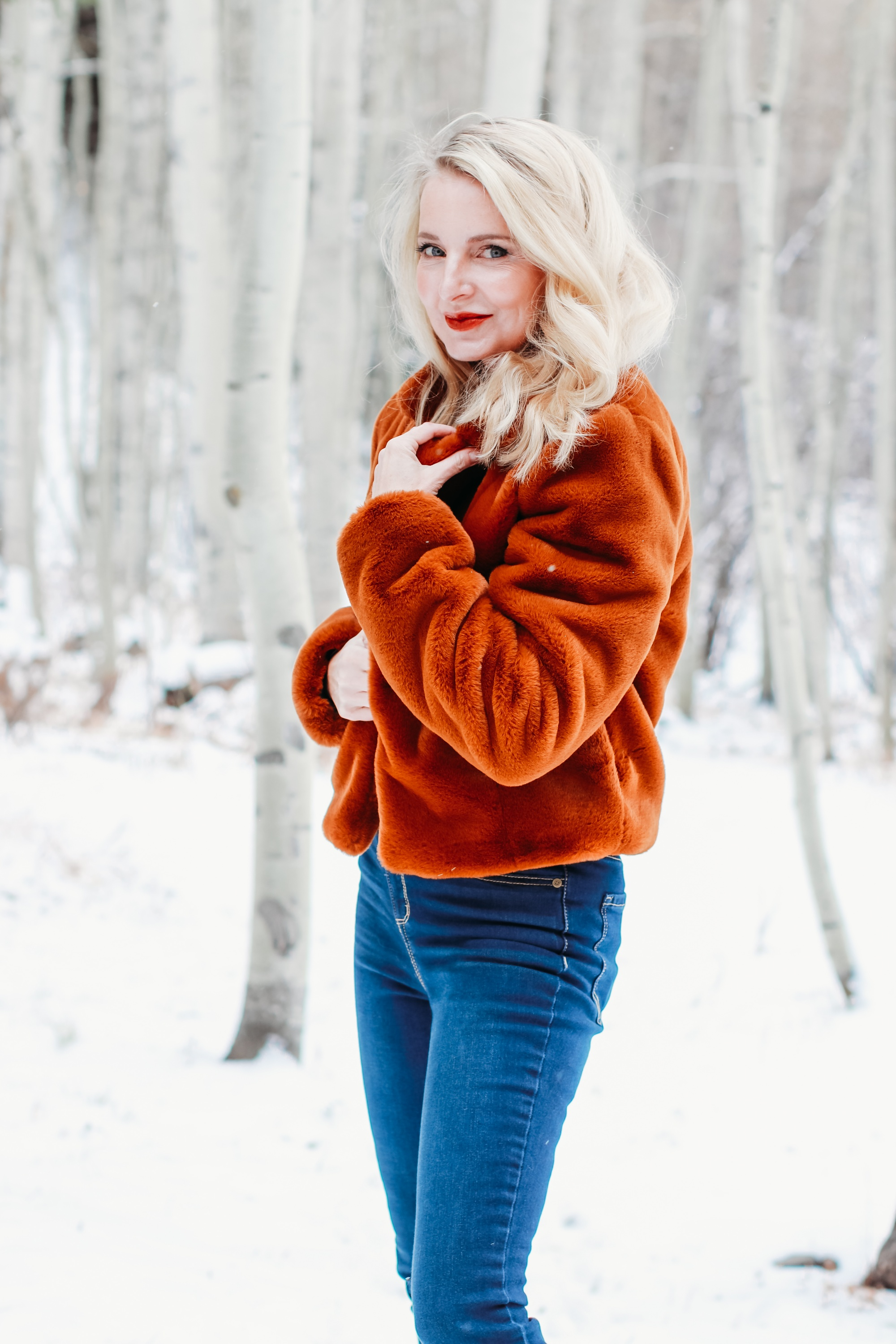 How to Wear Faux fur coat, Erin Busbee of Busbee Style wearing a brwon Blank NYC faux fur jacket with ribbed ruched sleeve sweater and dark wash skinny jeans from Express and Mou woven snow boots standing in the snow in Telluride, Colorado