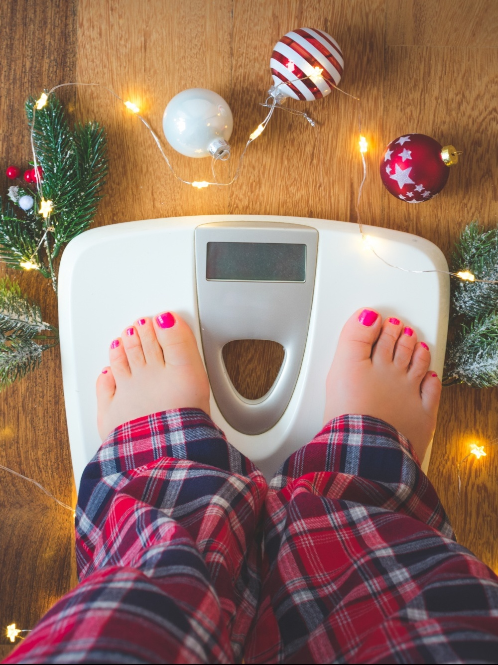 Woman's legs in plaid pj pants standing on bathroom scale surrounded by Christmas ornaments