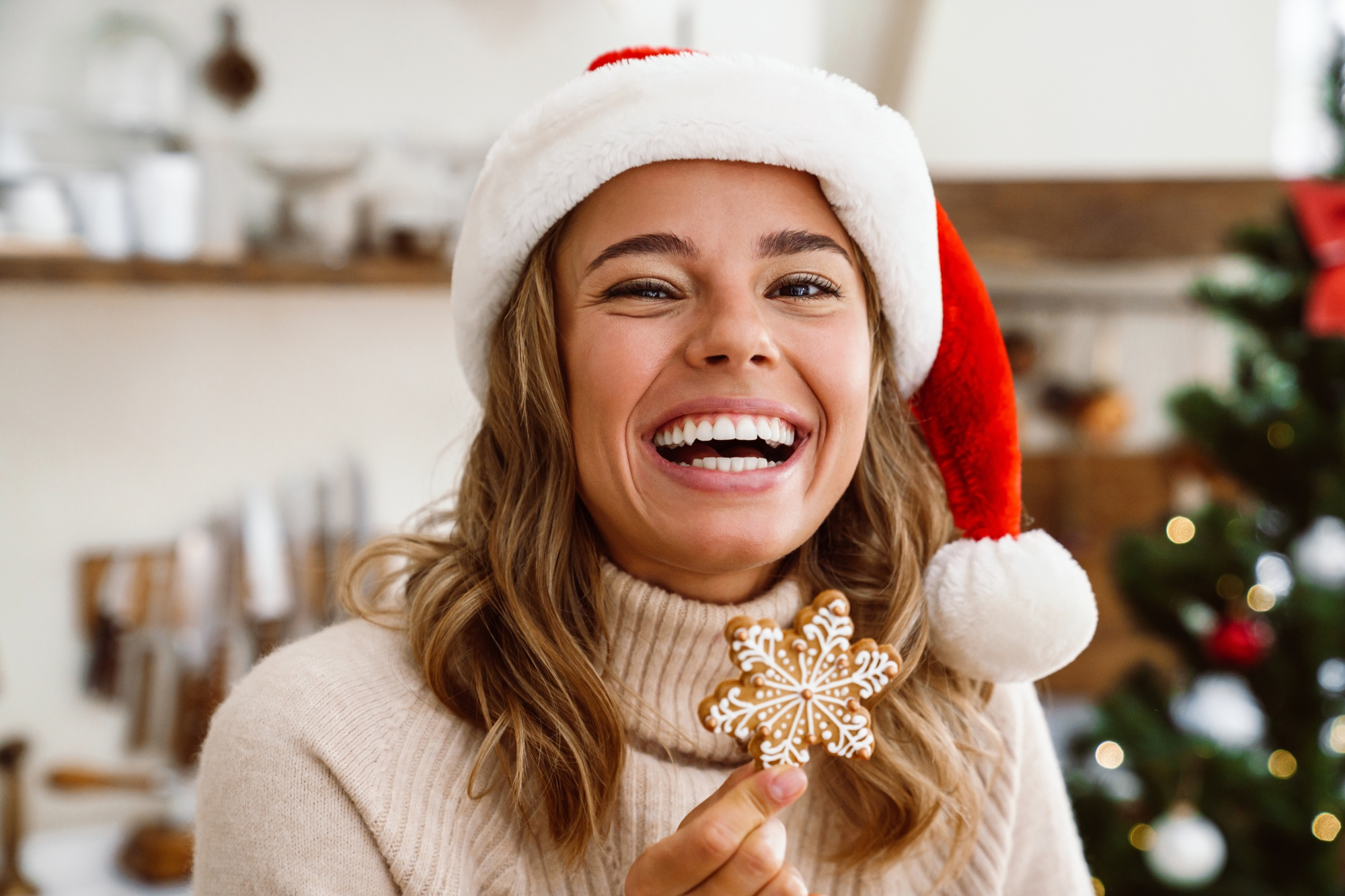 Happy cute woman in santa claus hat laughing and eating Christmas cookie in cozy kitchen