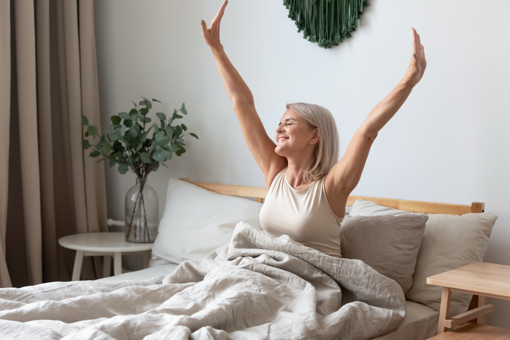 positive things about menopause, Aged female waking up in morning stretches seated in bed