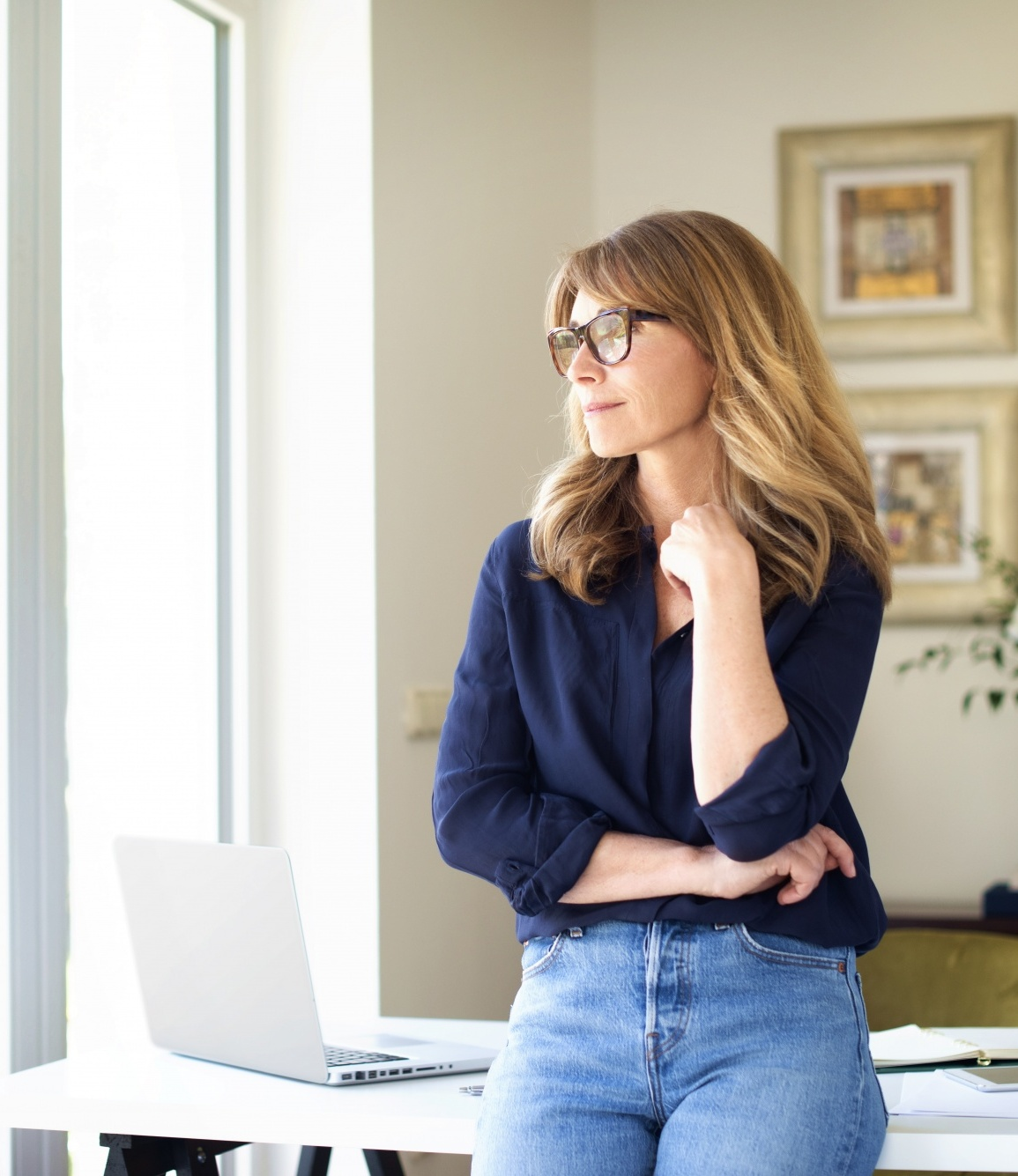 Starting a self care routine, Portrait shot of thinking mature woman standing at desk at home while looking out the window.