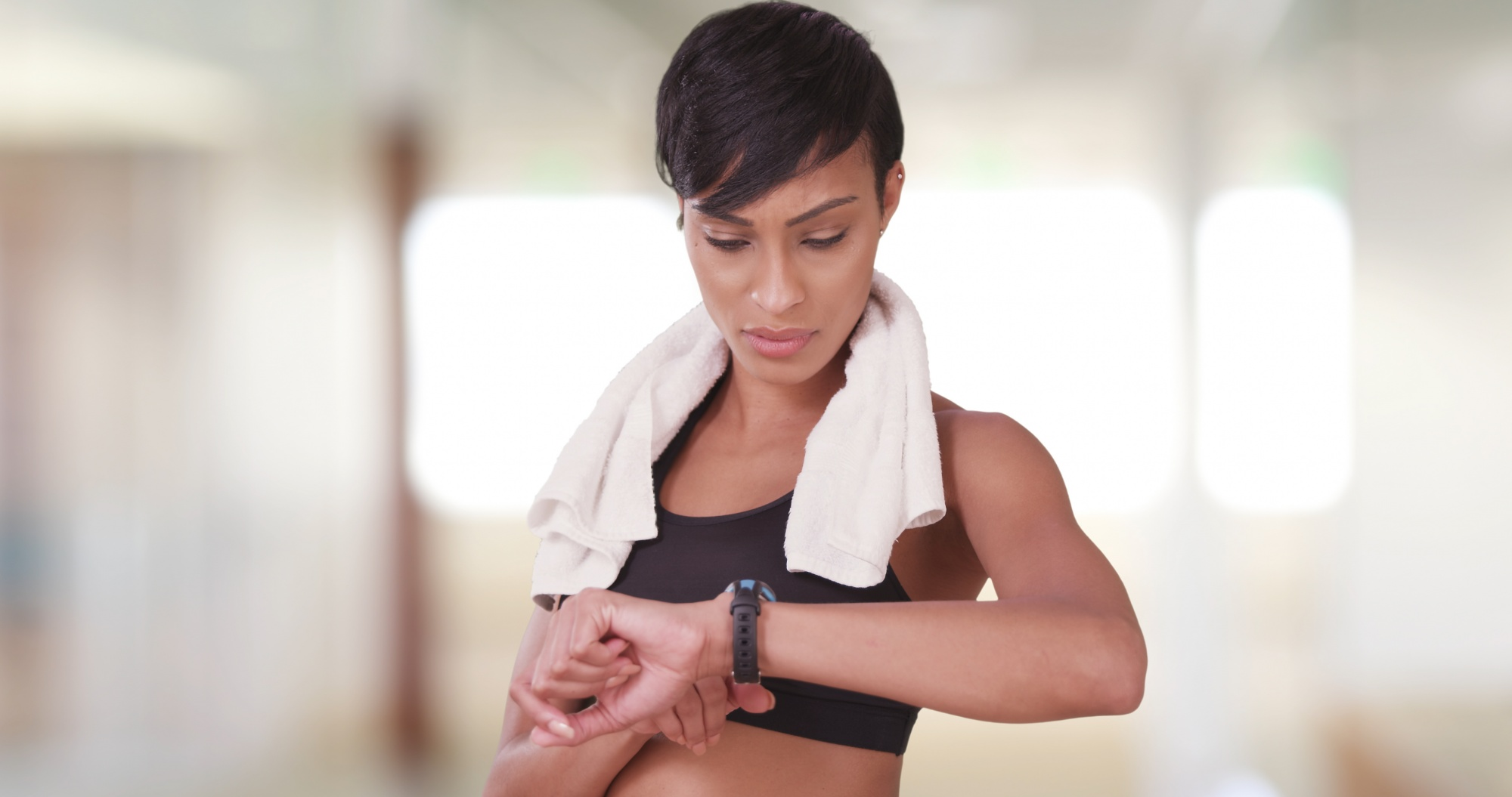 Starting a self care routine, Black woman in gym using smart watch to check heart rate