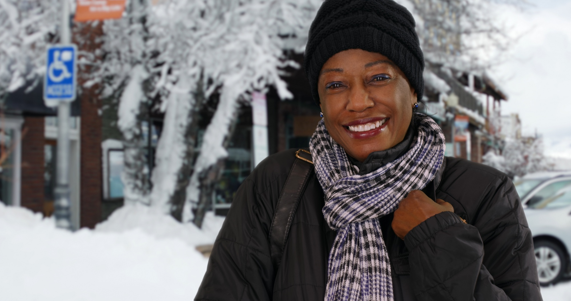 benefits of being outside during winter, Black woman in a black hat and jacket on a snowy sidewalk
