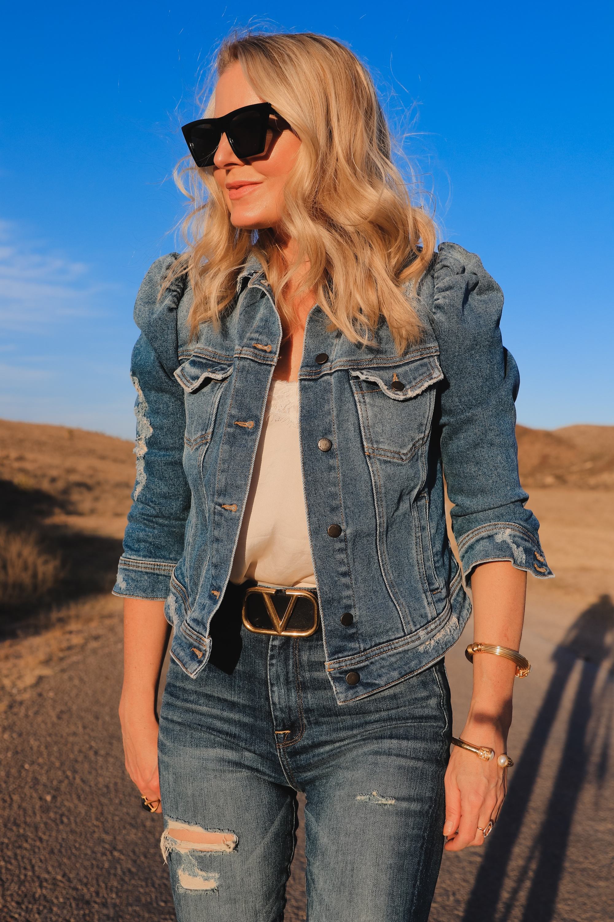 How To Wear Denim on Denim, Erin Busbee of Busbee wearing a distressed puff sleeve denim jacket by Retrofete, 7 For All Mankind distressed jeans, black Alexander Wang cutout booties, white B.P. lace cami, black cat eye sunglasses, and Julie Vos gold cuff bracelets in West Texas