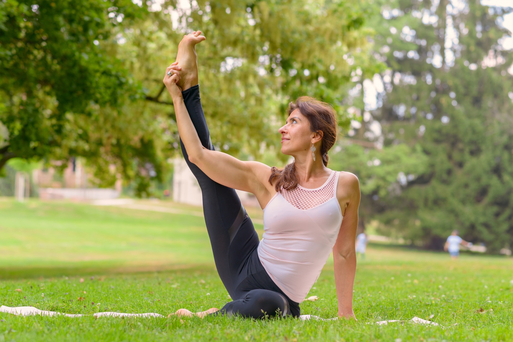 Starting a self care routine, Female adult yoga artist with brown hair doing leg exercises in meadow on top of white mat during the daytime
