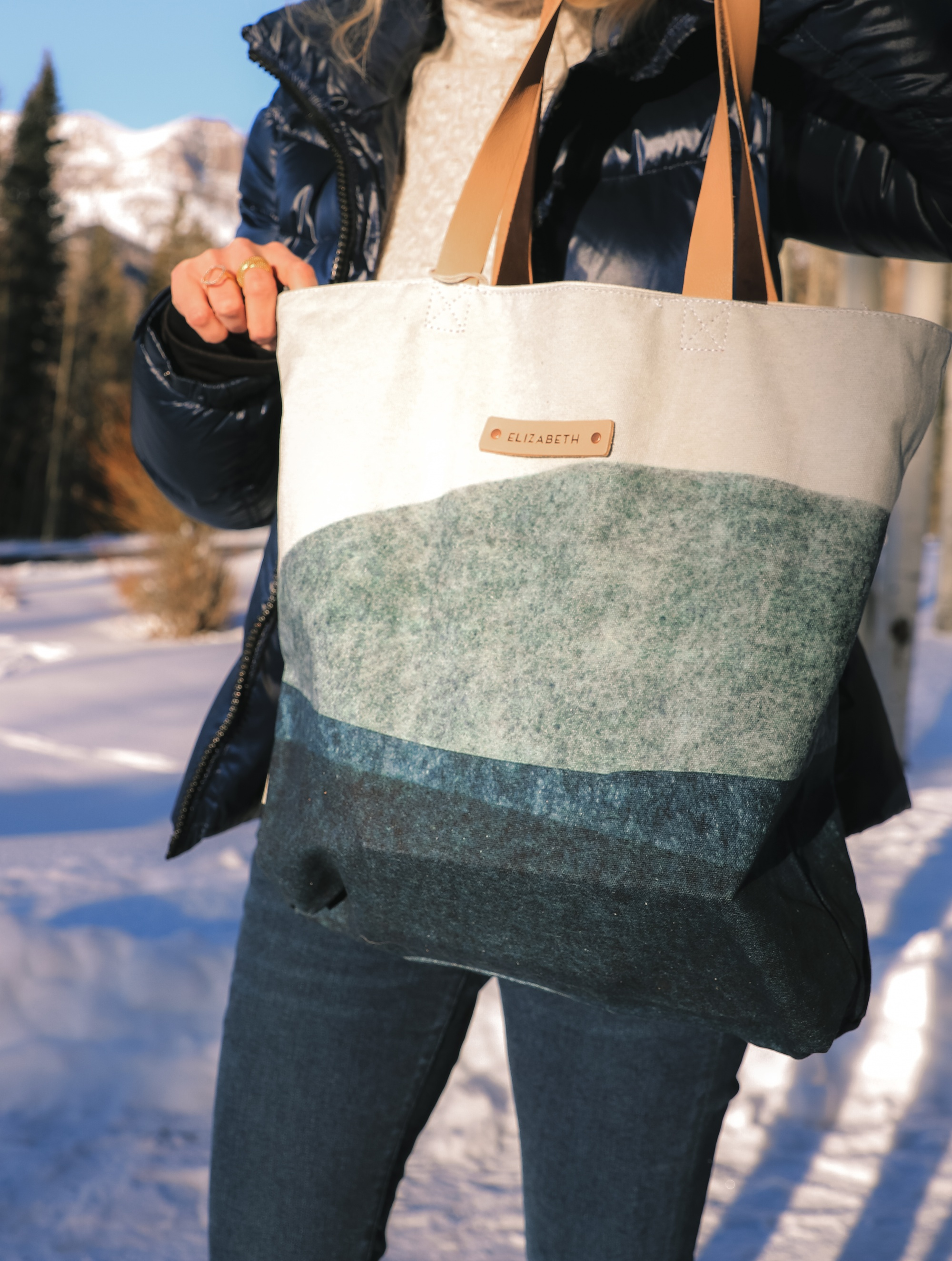 Personalized Gifts, Erin Busbee of Busbee Style carrying a blue and white personalized tote bag from Minted wearing a SAM. puffer jacket with a cable knit sweater and jeans in Telluride, Colorado